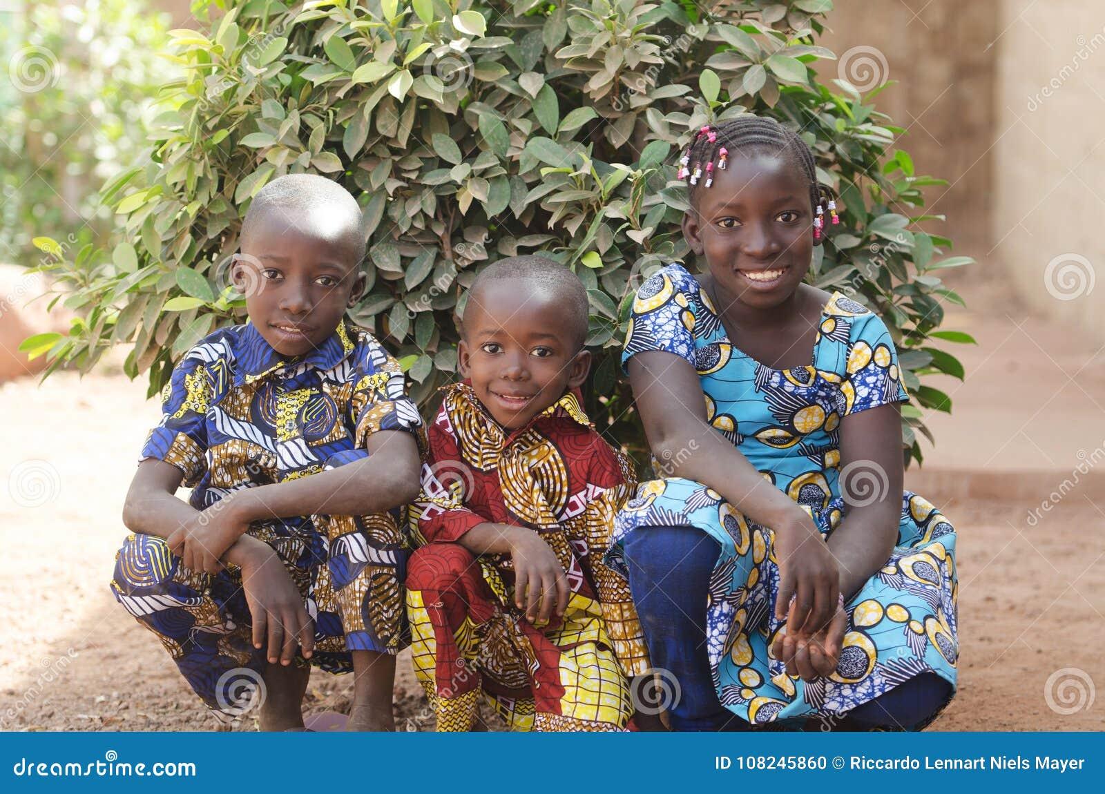 Três crianças africanas lindos que levantam fora o sorriso e o Laug