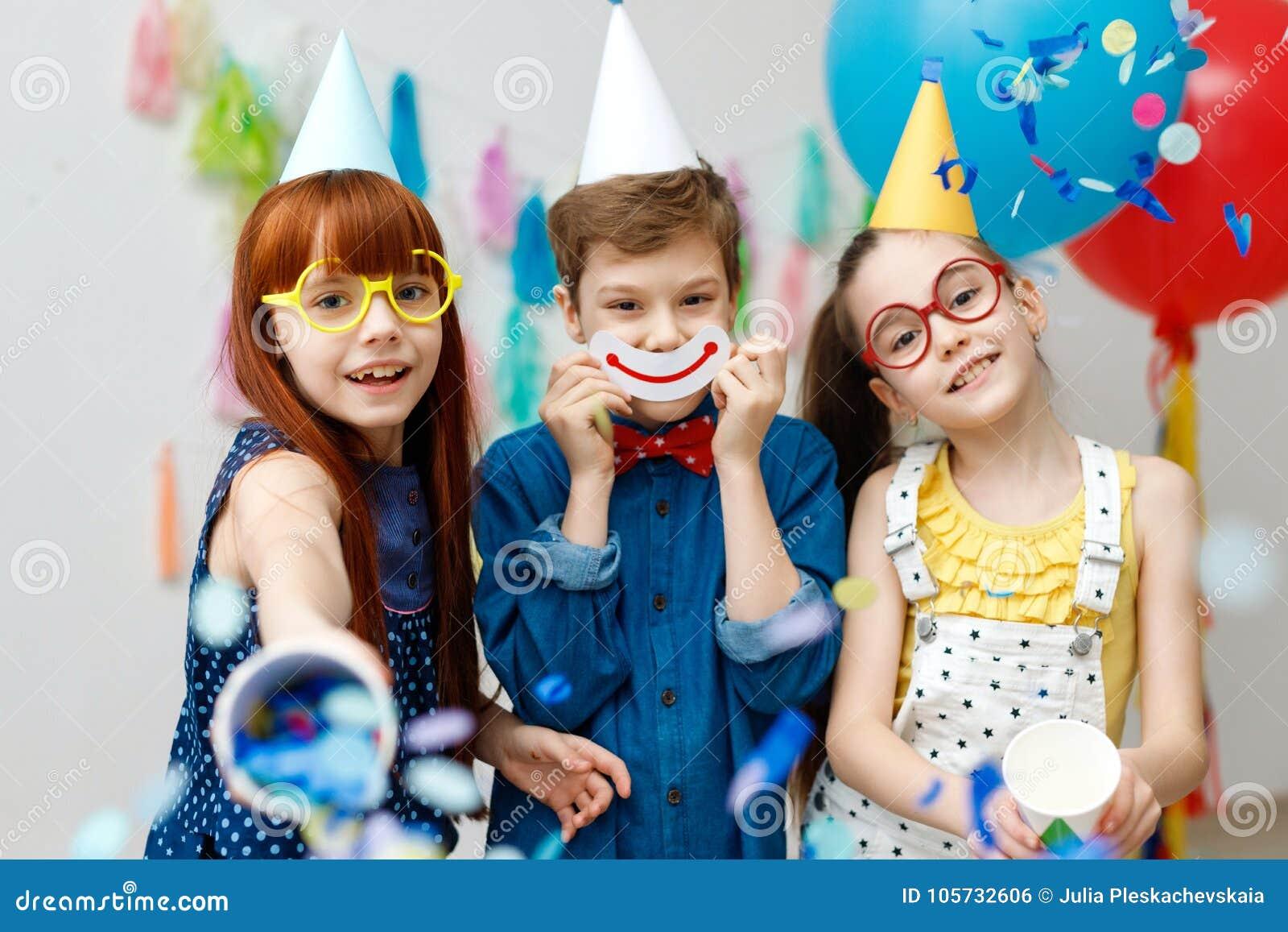 Três crianças amigáveis nos tampões festivos do cone e no eyewear grande, suporte na sala decorativa com balões, têm o divertimen