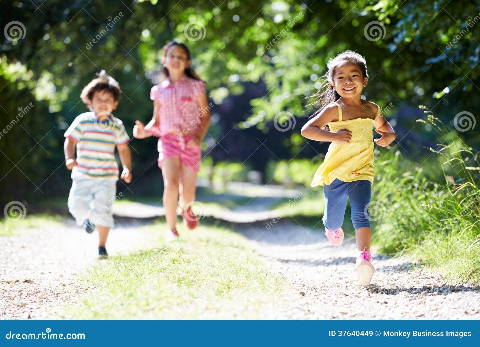 Três crianças asiáticas que apreciam a caminhada no campo