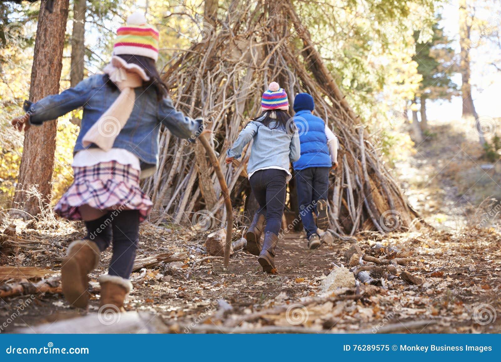 Três crianças jogam fora do abrigo feito dos ramos em uma floresta