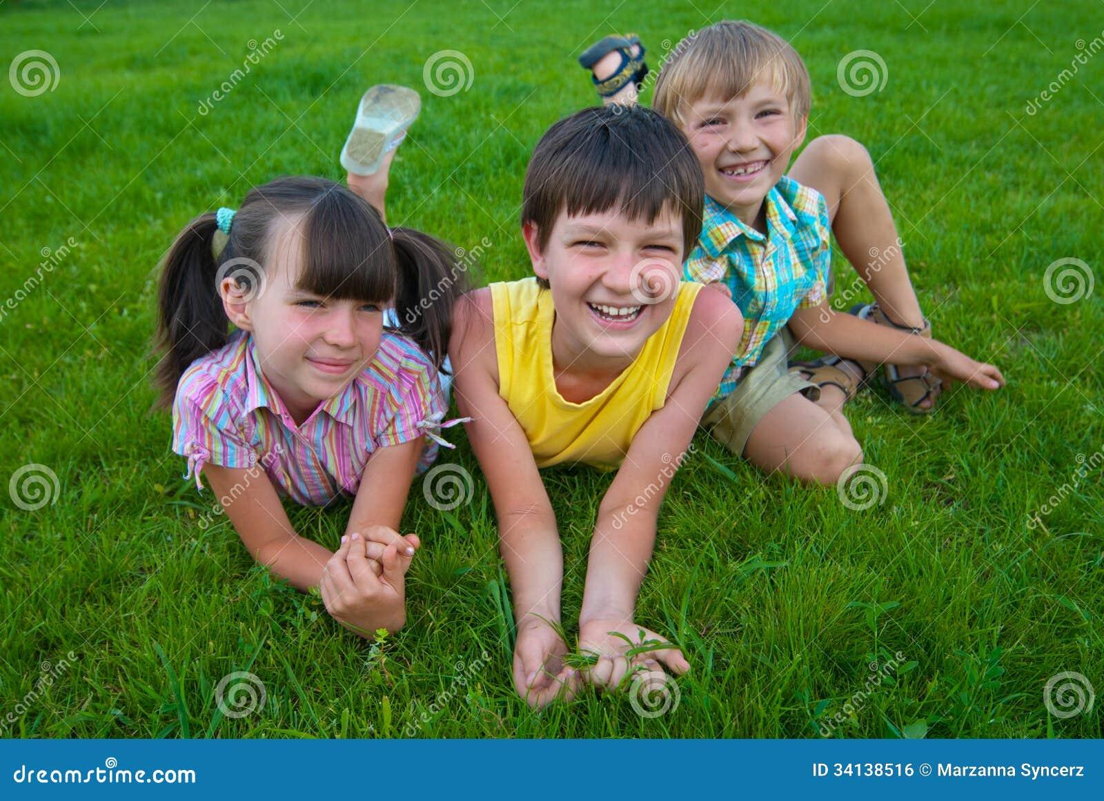 Três crianças na grama