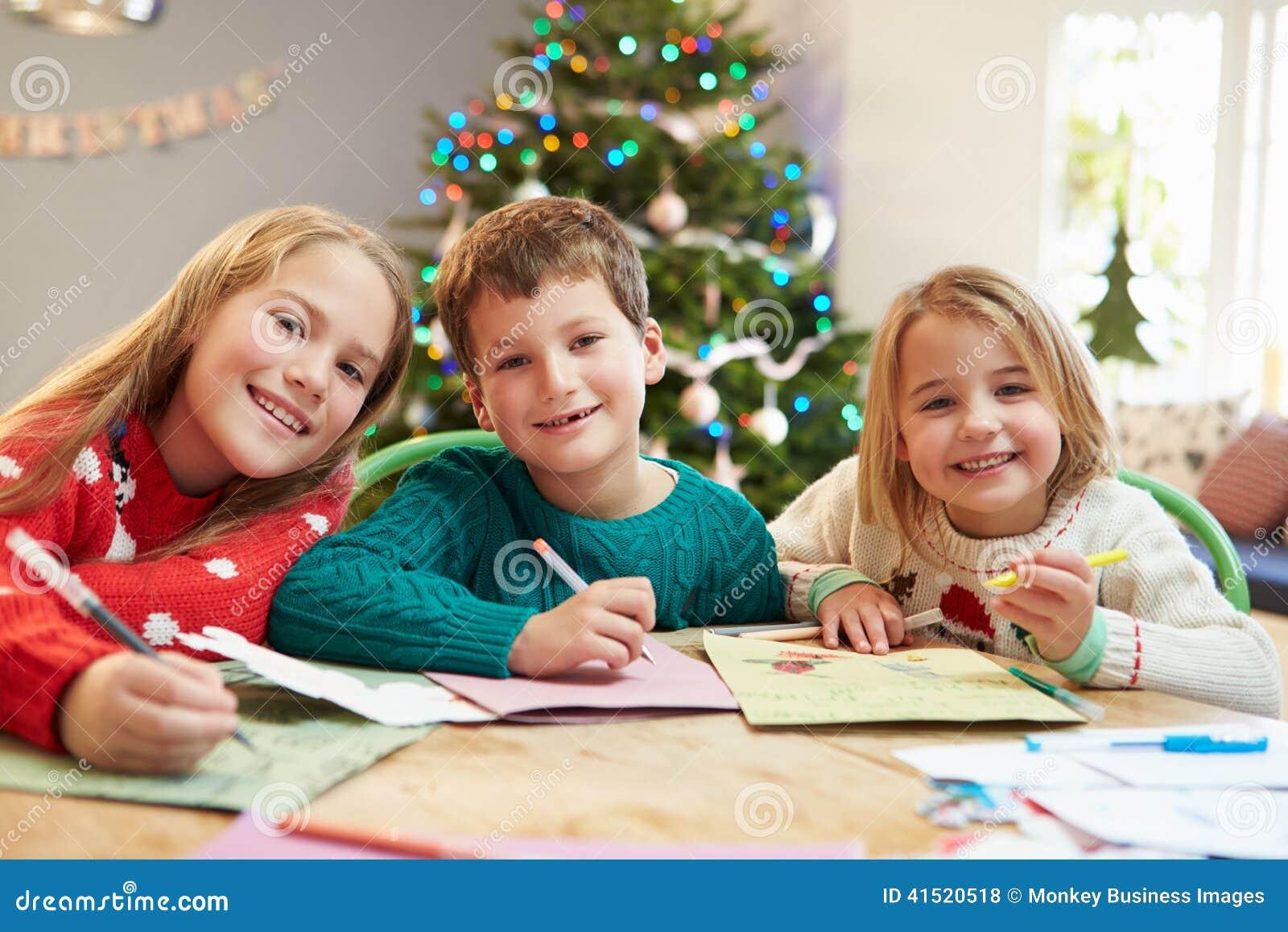 Três crianças que escrevem letras a Santa Together