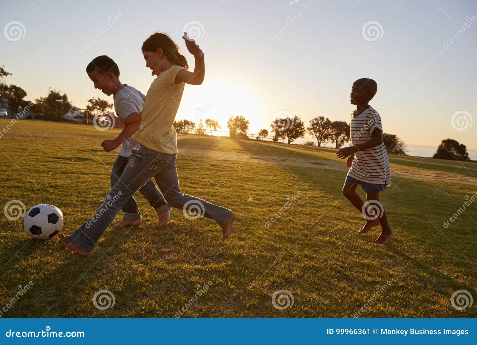 Três crianças que jogam o futebol em um campo