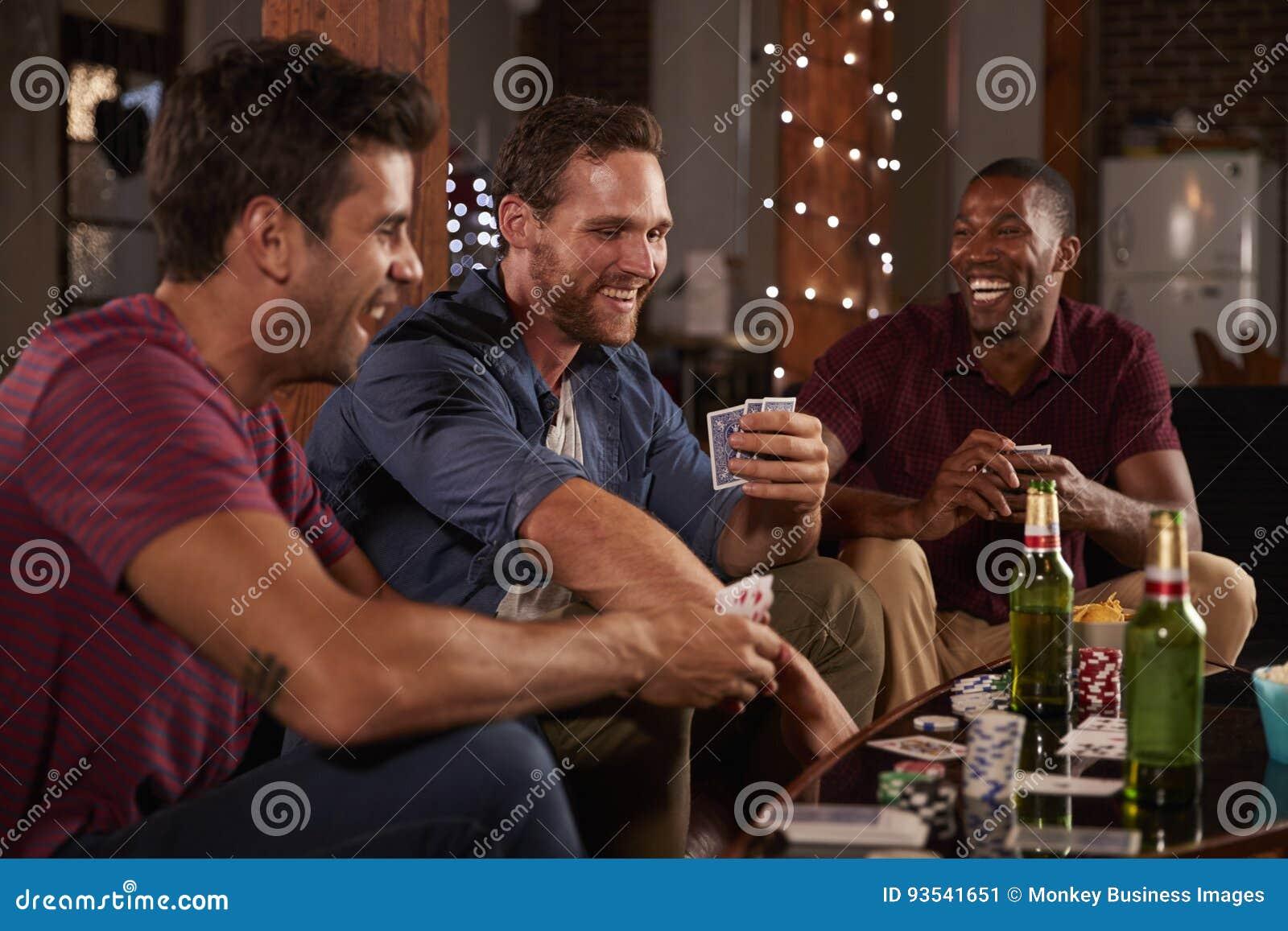 Três dos amigos de jogo masculinos e rir cartões em casa
