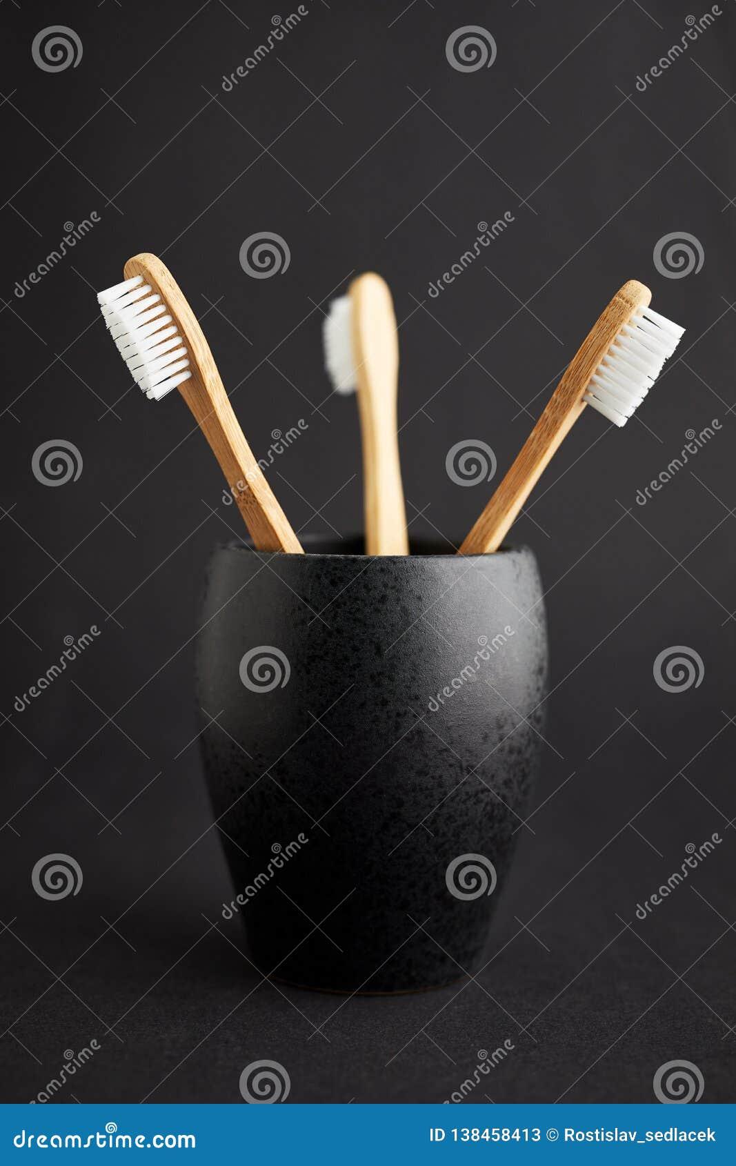 Três escovas de dentes de bambu em um vidro preto