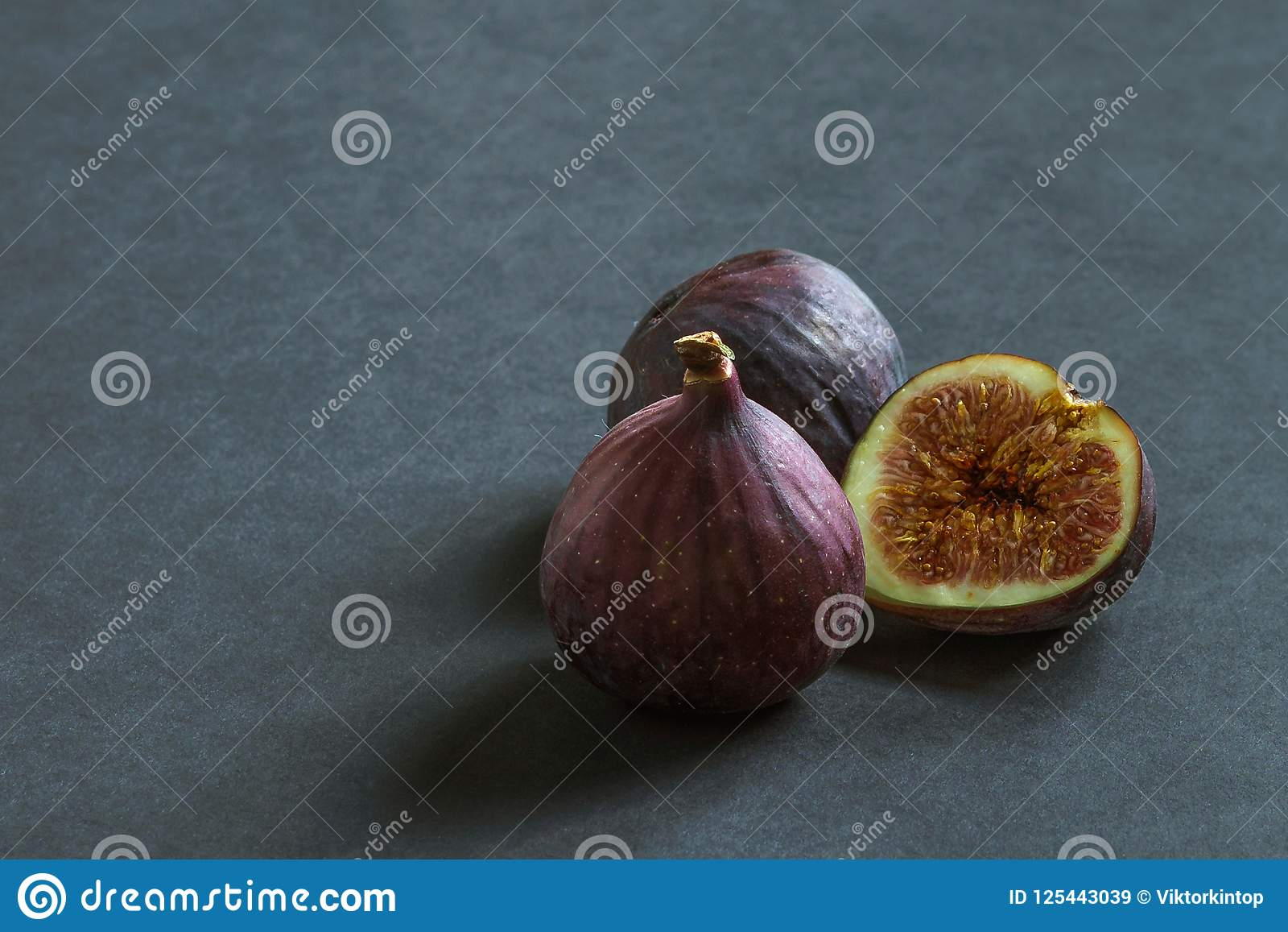 Três frutos maduros do figo em um fundo cinzento