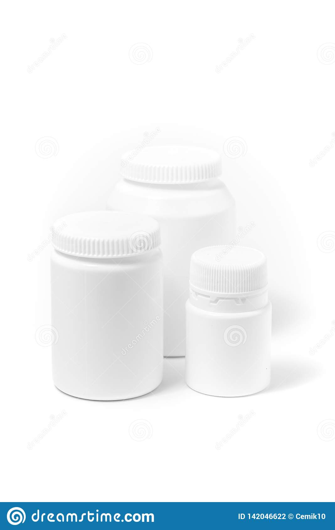 Três garrafas dos comprimidos brancos da medicina isolados no branco