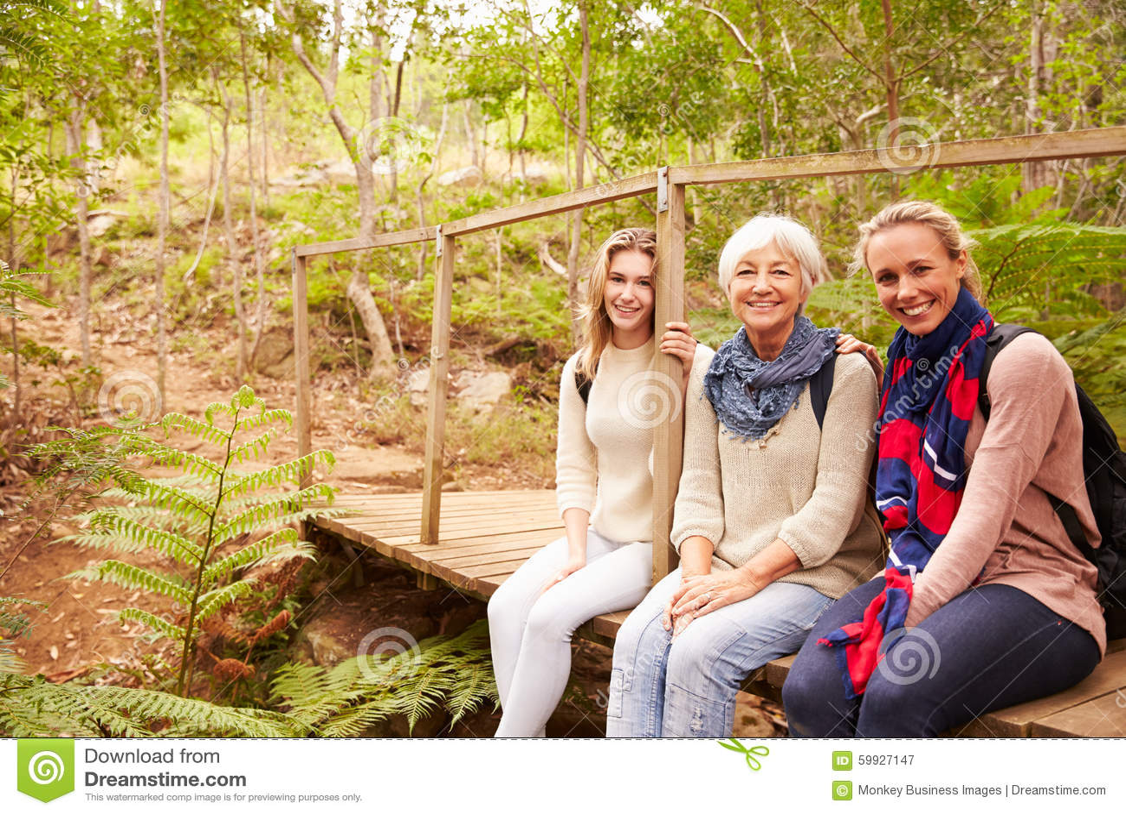 Três gerações de mulheres que sentam-se em uma floresta, retrato