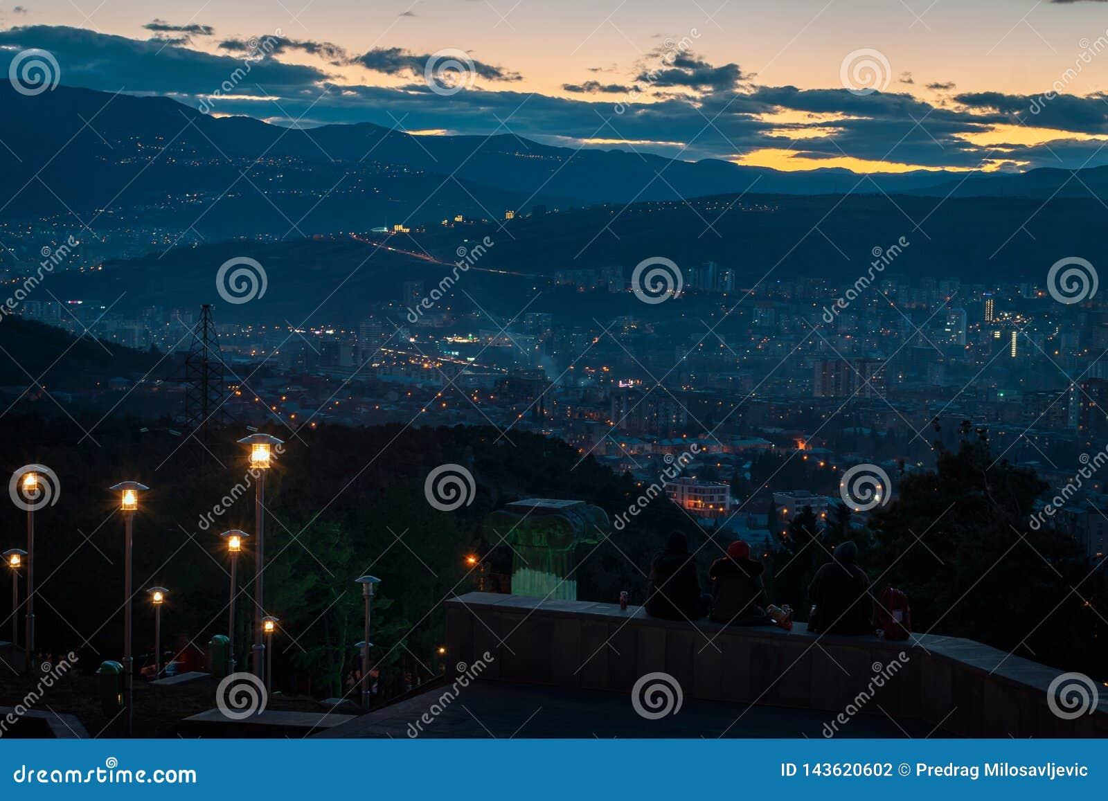 Três jovens que sentam-se sobre o monte que negligencia a capital de Geórgia, Tbilisi quando o sol for para baixo atrás do monte