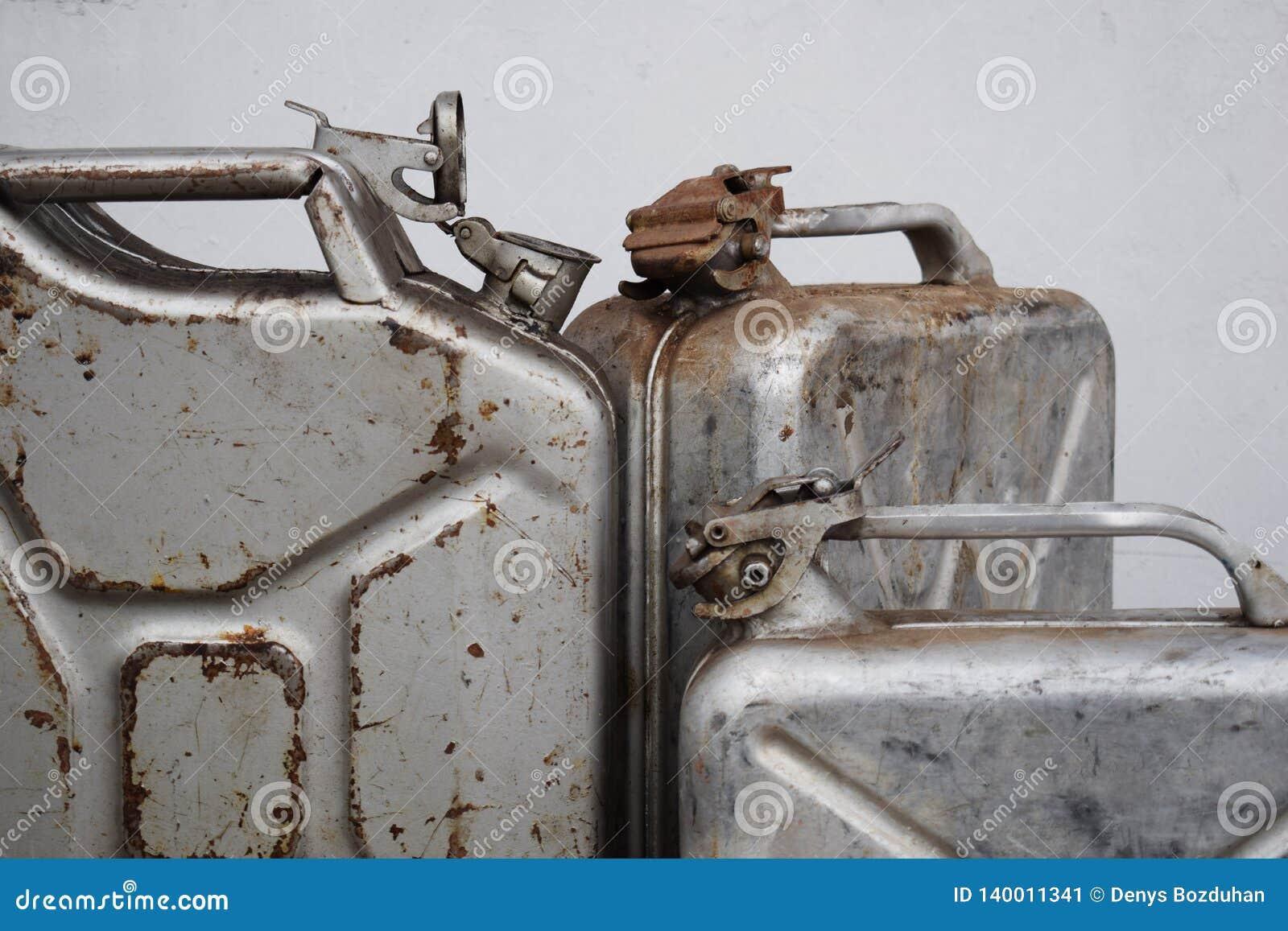 Três latas cinzentas com gasolina ou diesel, tambor do metal
