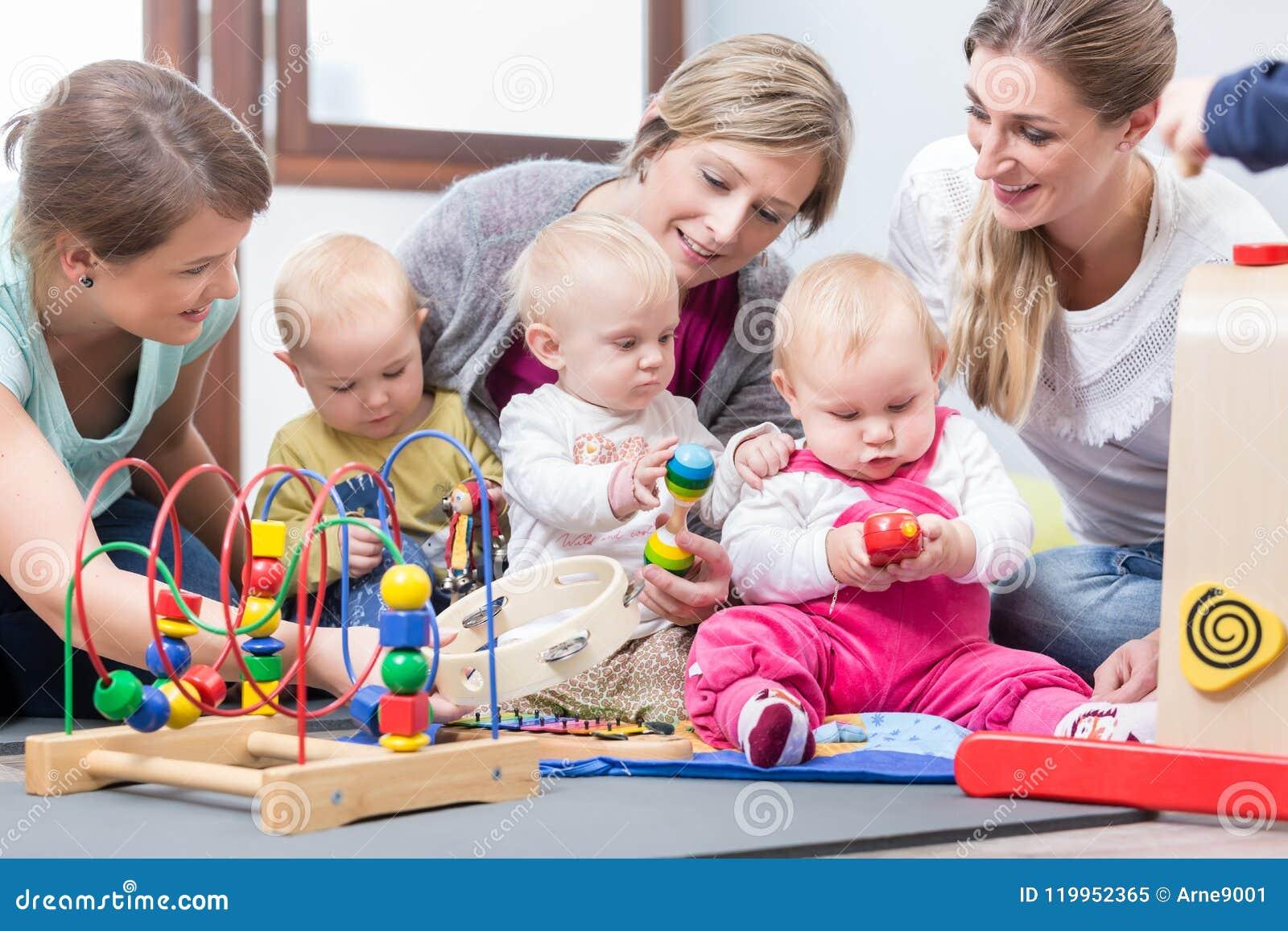 Três mães felizes que olham seus bebês jogar com brinquedos seguros