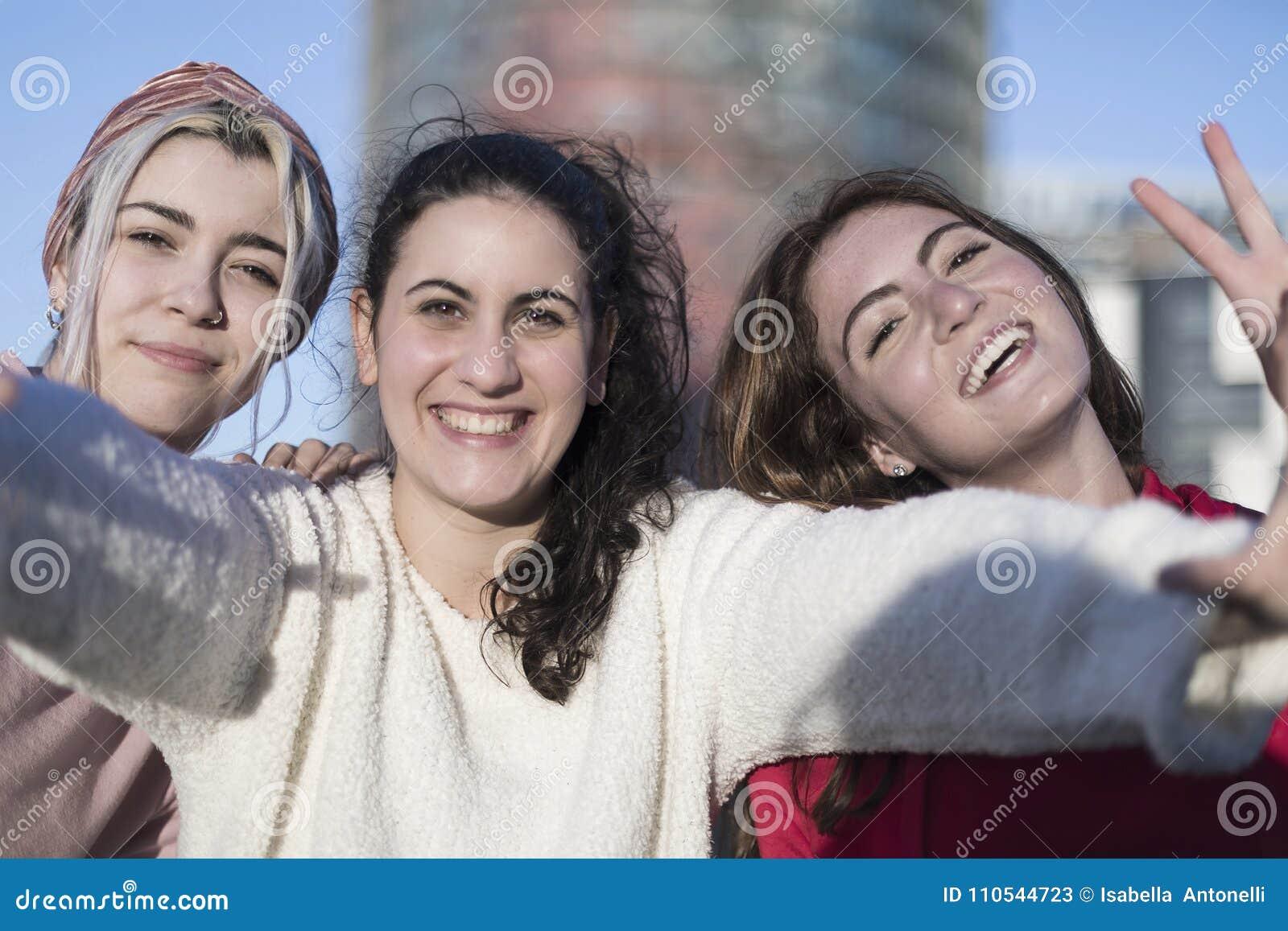 Três melhores amigas felizes que fazem fora o selfie no smartphon