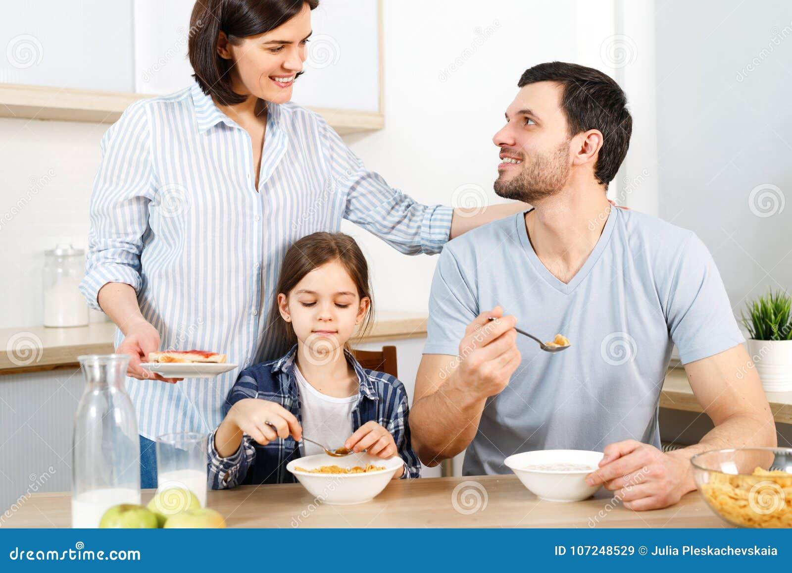 Três membros da família têm o café da manhã saudável delicioso na cozinha, comem flocos de milho com leite, apreciam a unidade e