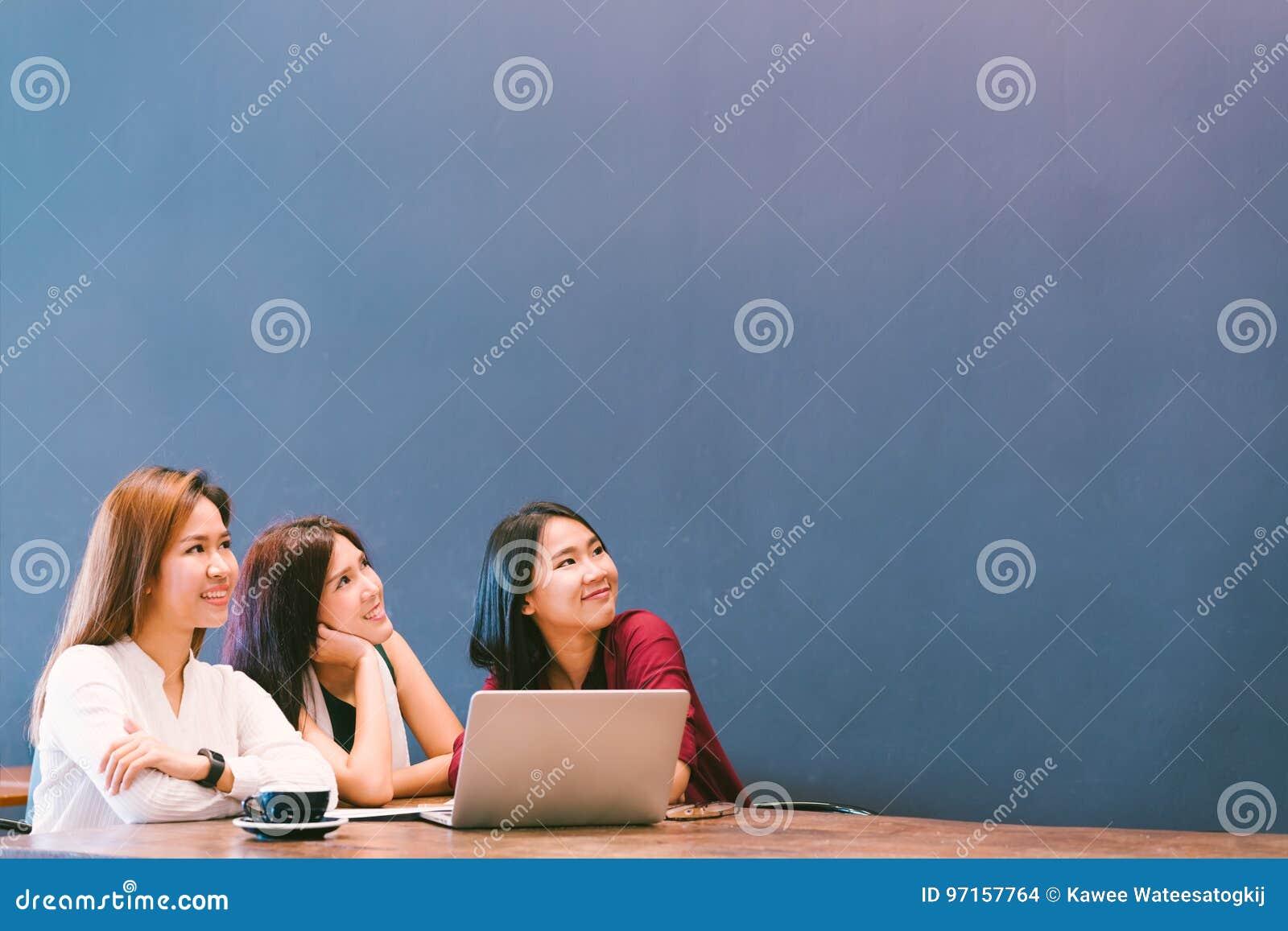 Três meninas asiáticas bonitas que olham para cima para copiar o espaço ao trabalhar no café, estilo de vida moderno com conceito