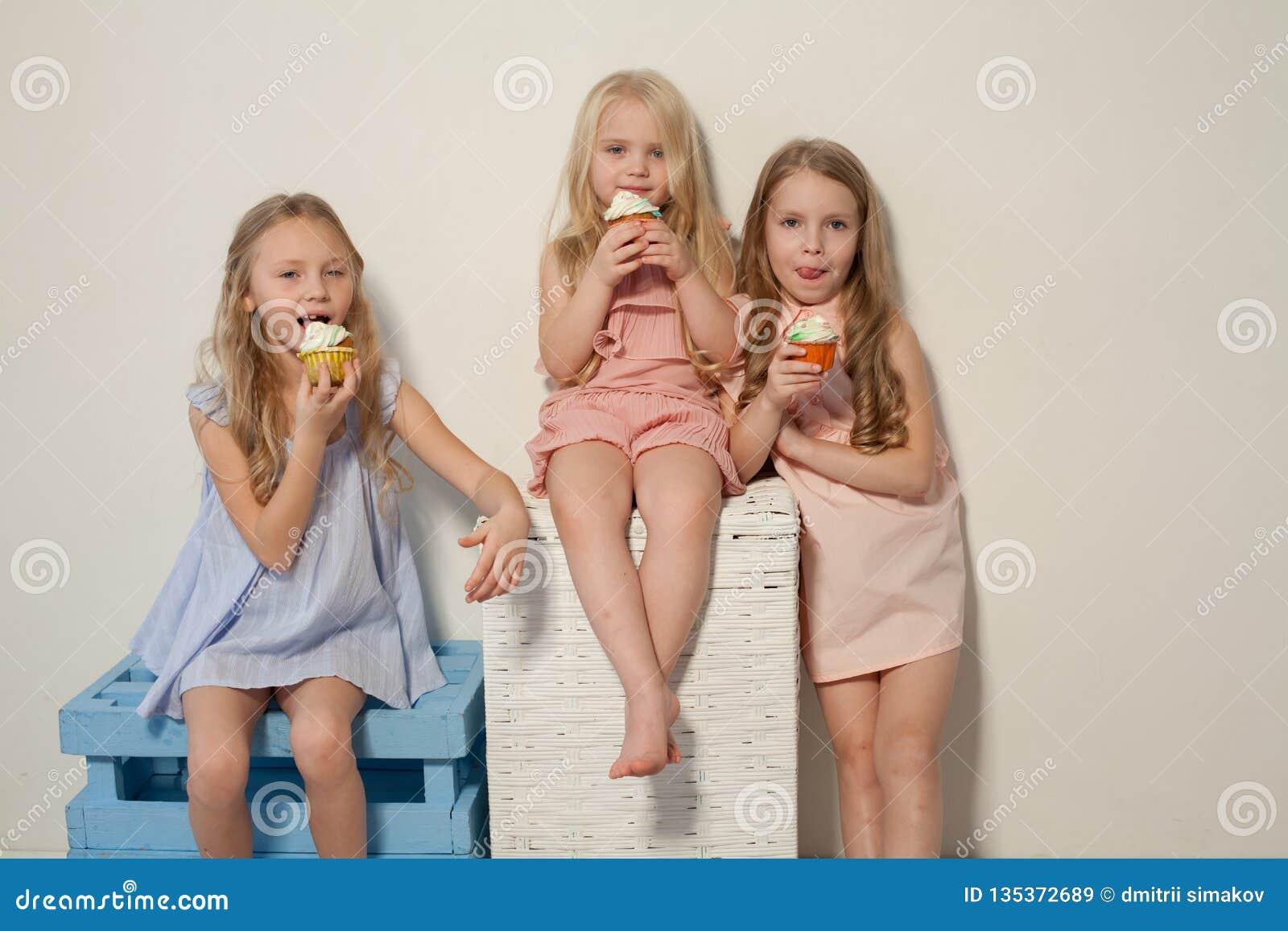 Três meninas comem o bolo doce com queque de creme