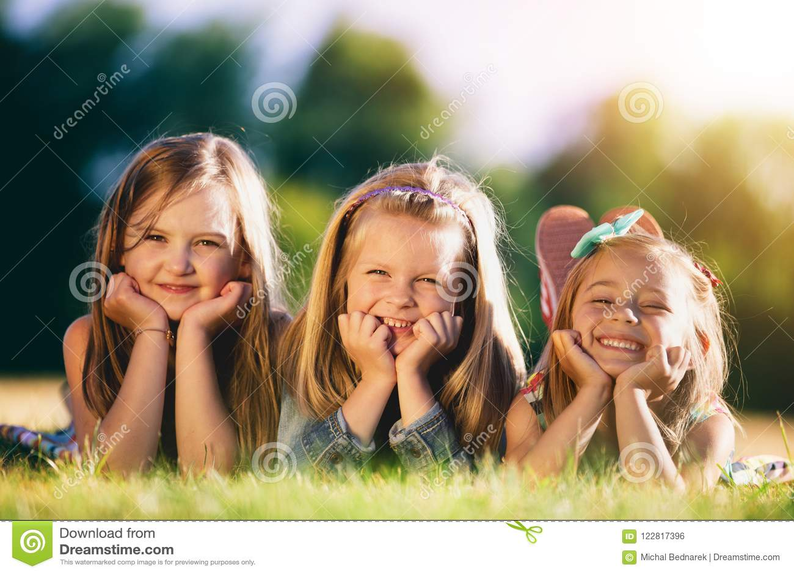 Três meninas de sorriso que colocam na grama no parque