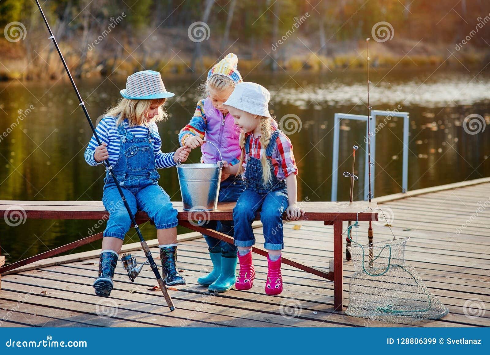 Três meninas felizes pequenas vangloriam-se sobre os peixes travados em um polo de pesca Pesca de um pontão de madeira