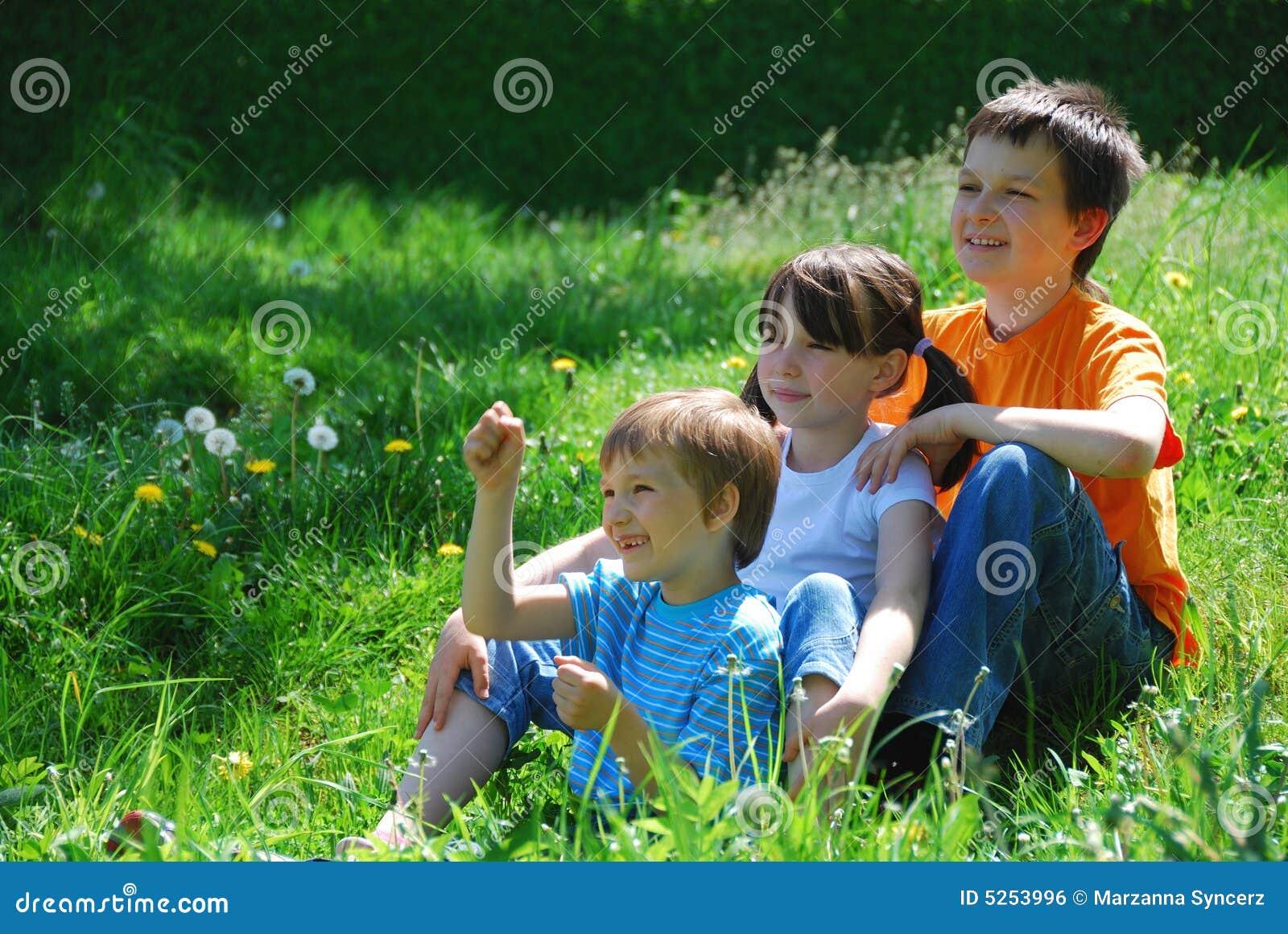 Três miúdos em um prado