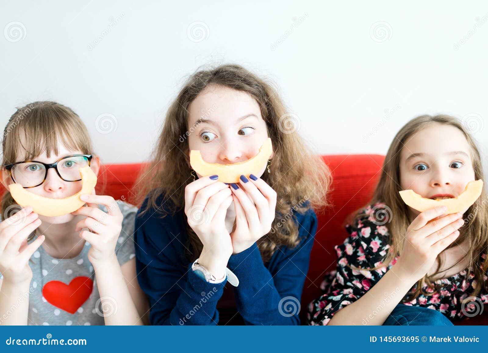 Três moças que sentam-se no sofá vermelho e que comem o melão amarelo