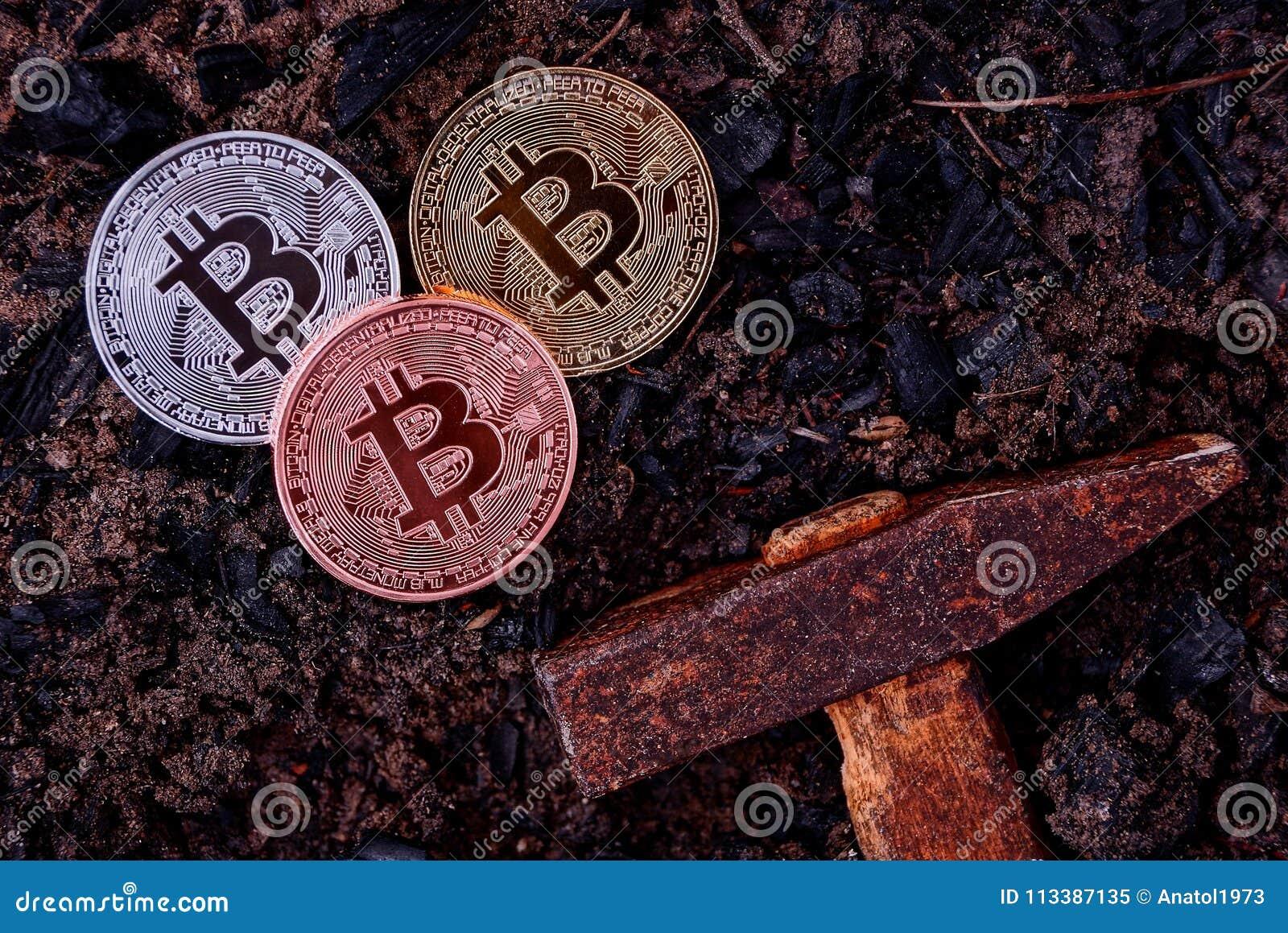 Três moedas do bitcoin na terra preta e em um martelo