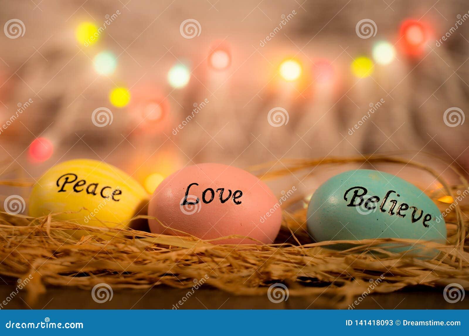 Três ovos da páscoa na cama da palha com palavras