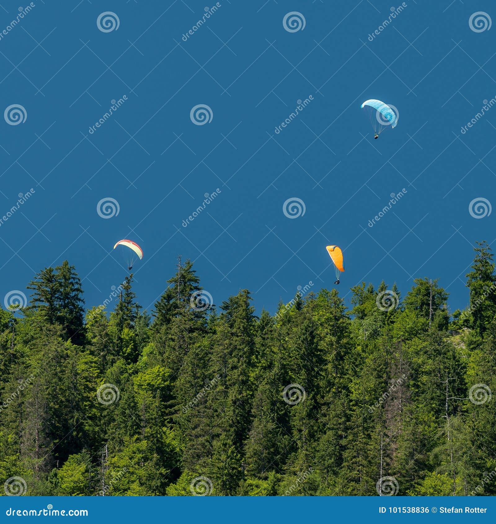 Três paragliders no céu azul das montanhas