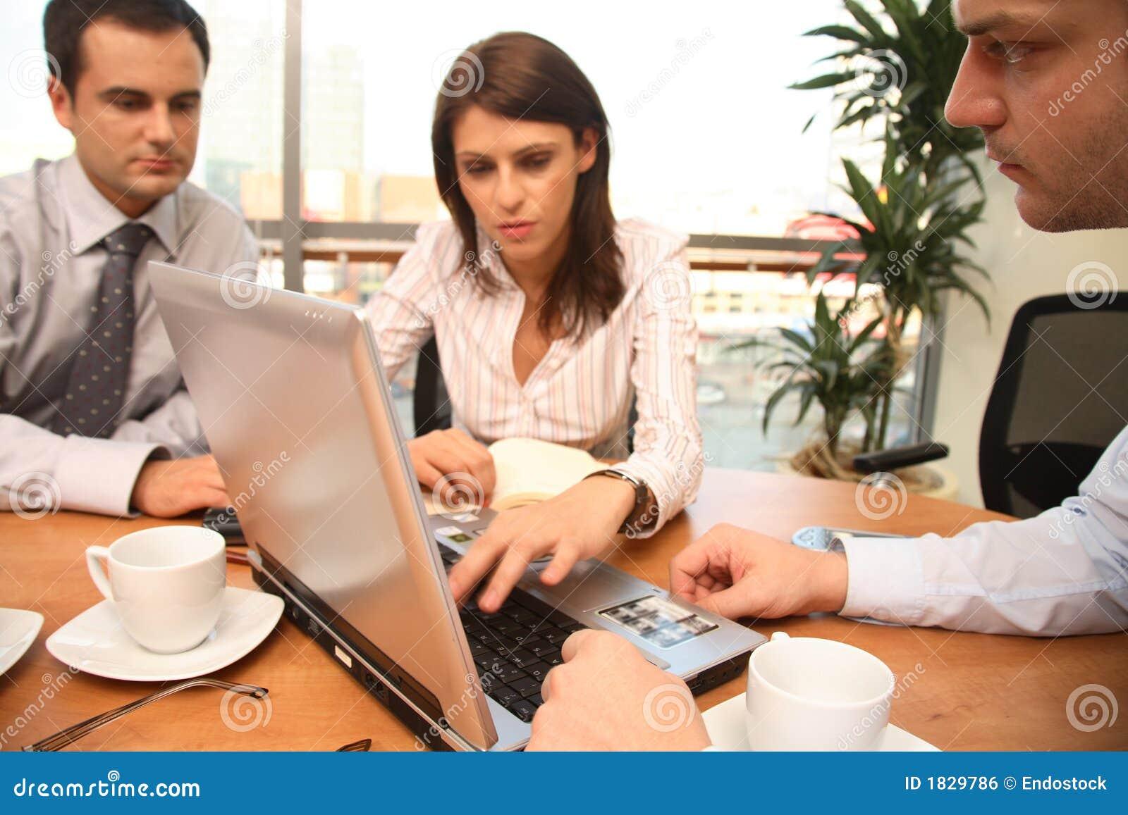 Três pessoas do negócio que trabalham junto com o portátil no escritório ensolarado