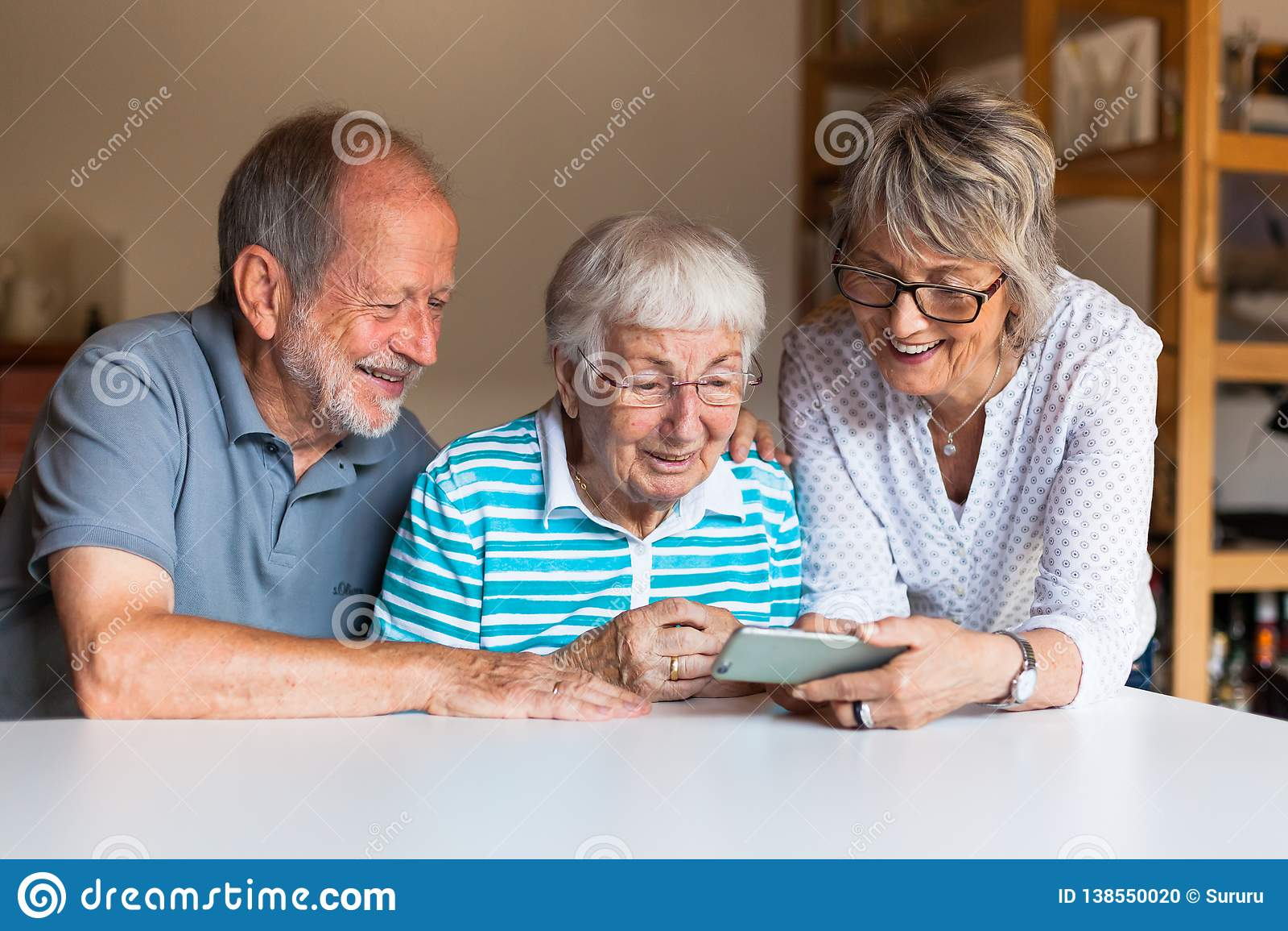 Três pessoas idosas que usam o telefone esperto