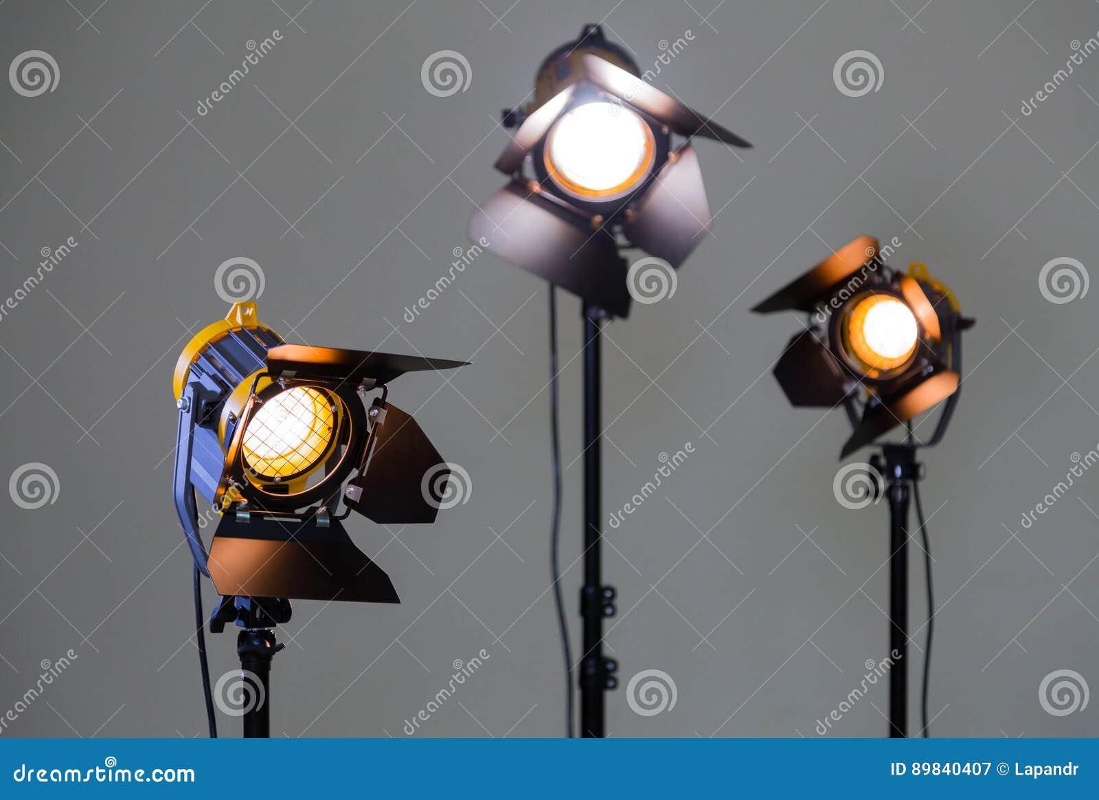 Três projetores do halogênio com lentes de Fresnel em um fundo cinzento Fotografia e filmar no interior