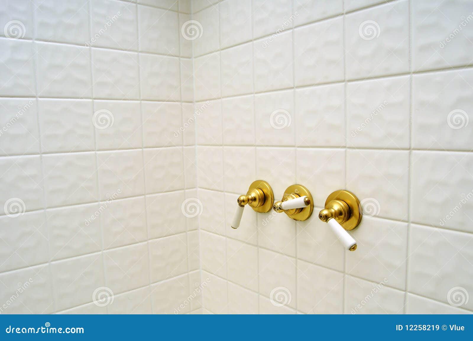 Três punhos dourados da válvula de chuveiro