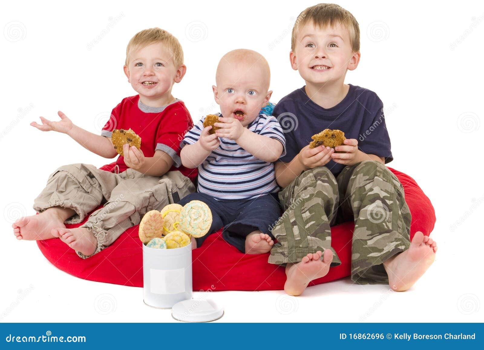 Três rapazes pequenos apreciam comer o bolinho