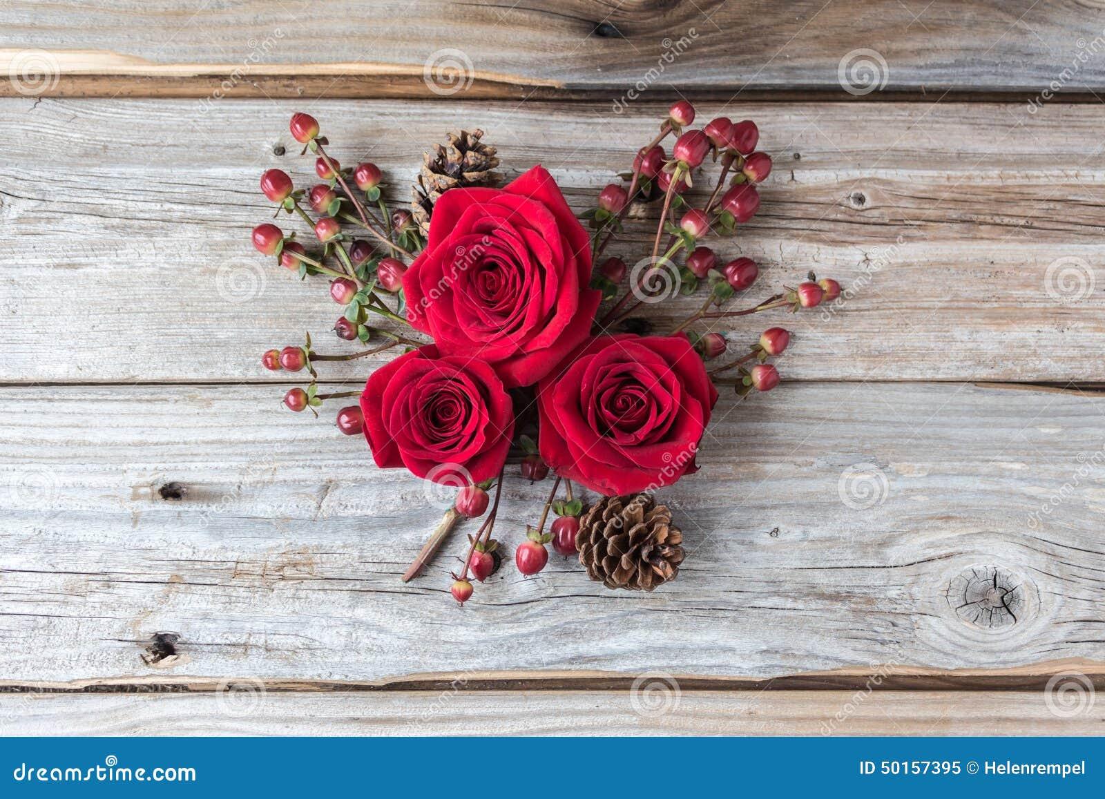 Três rosas vermelhas em um conjunto no fundo de madeira rústico