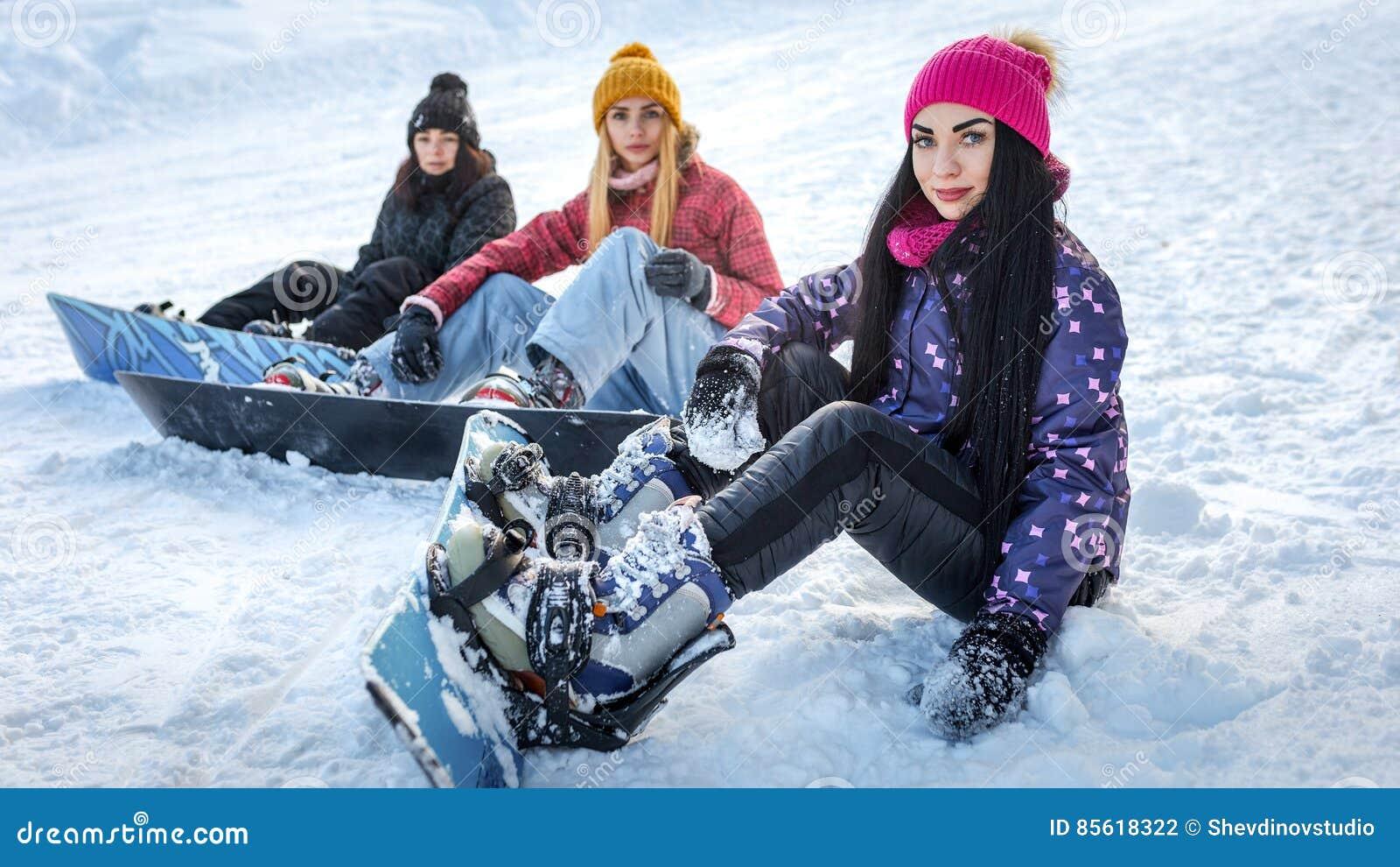 Três snowboarders das meninas que sentam-se na neve