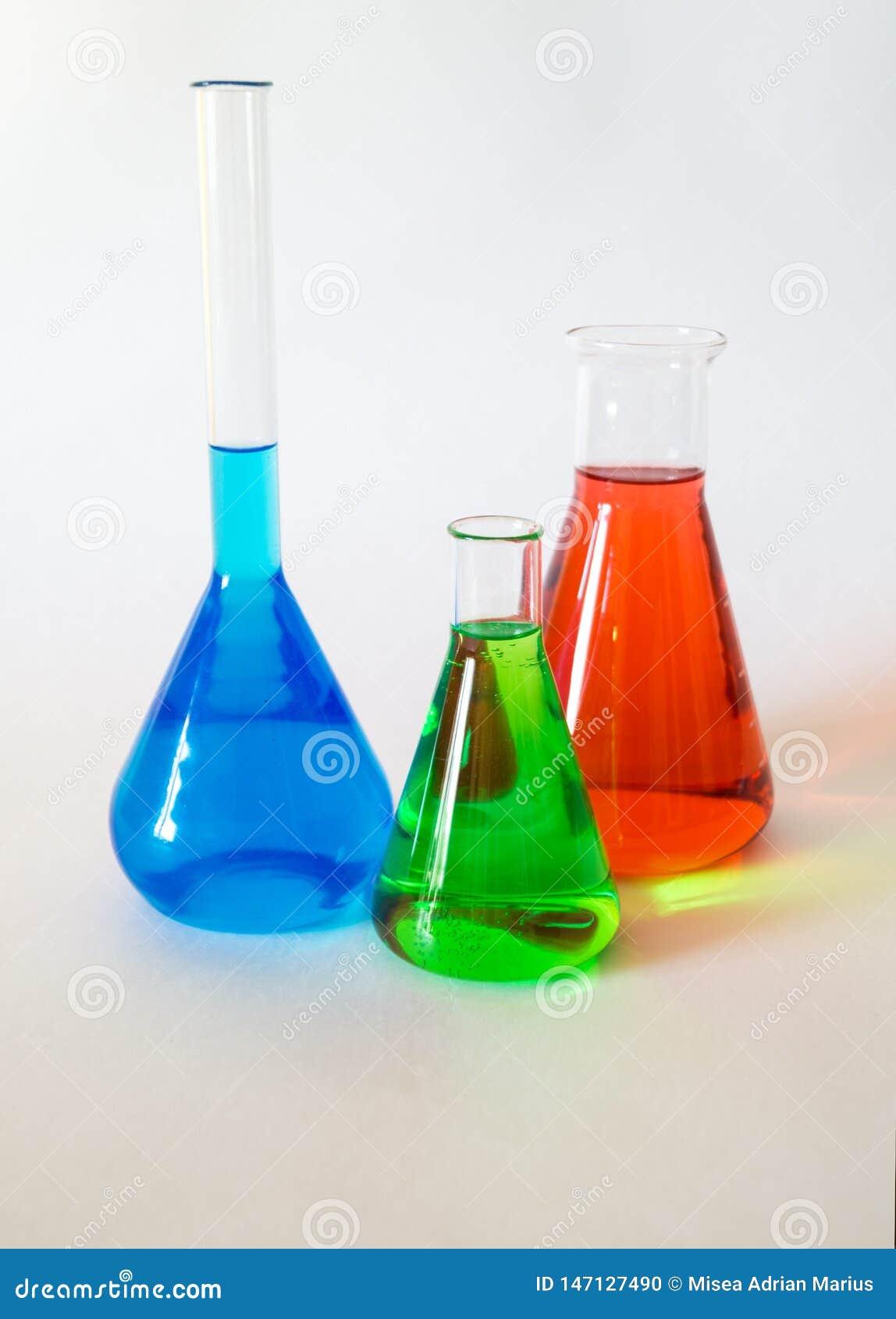 Três taças de vidro enchidas com o líquido colorido