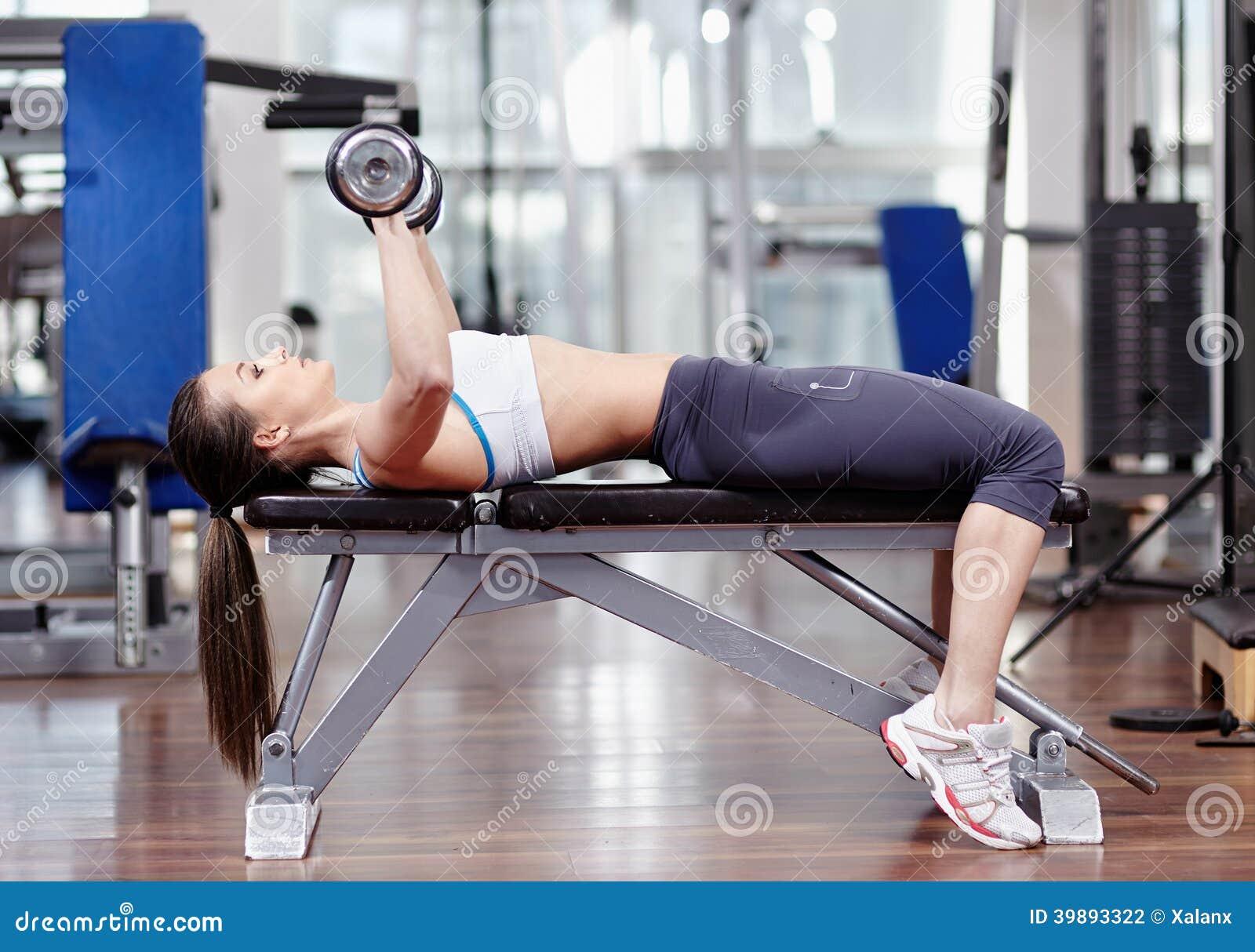 Tríceps y pecho de trabajo de la mujer con pesas de gimnasia