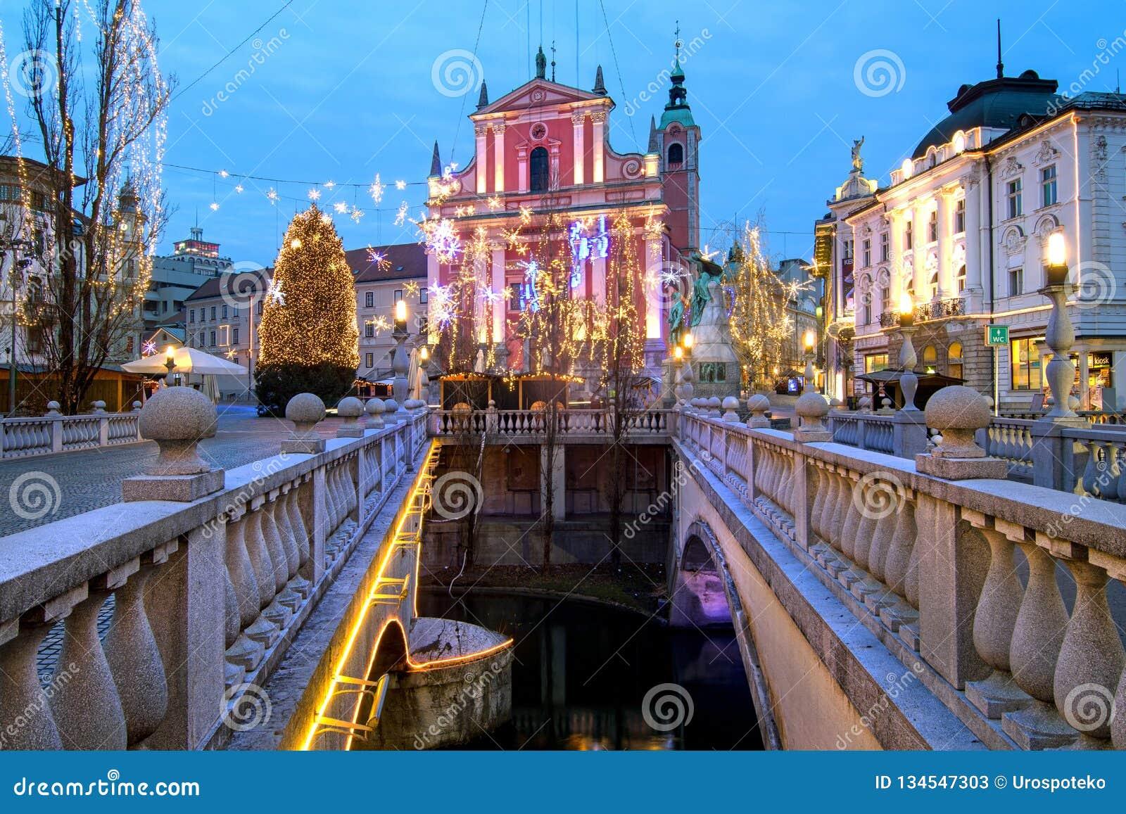 Trójka mosty choinka na Preseren kwadratowym i Franciszkański kościół, iluminujący dla bożych narodzeń i nowego roku świętowania,