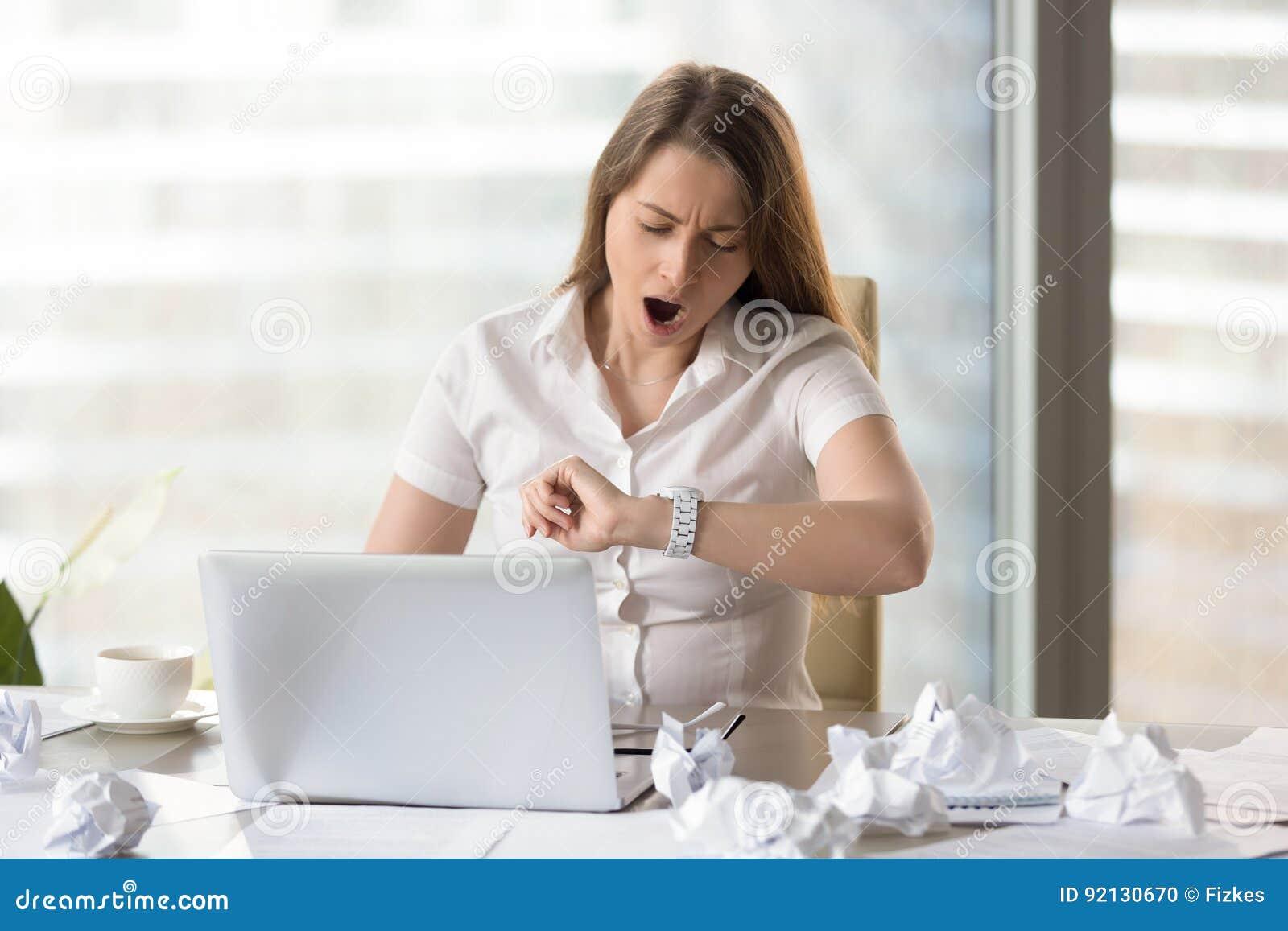Trött affärskvinna som väntar arbetsdagsändelse