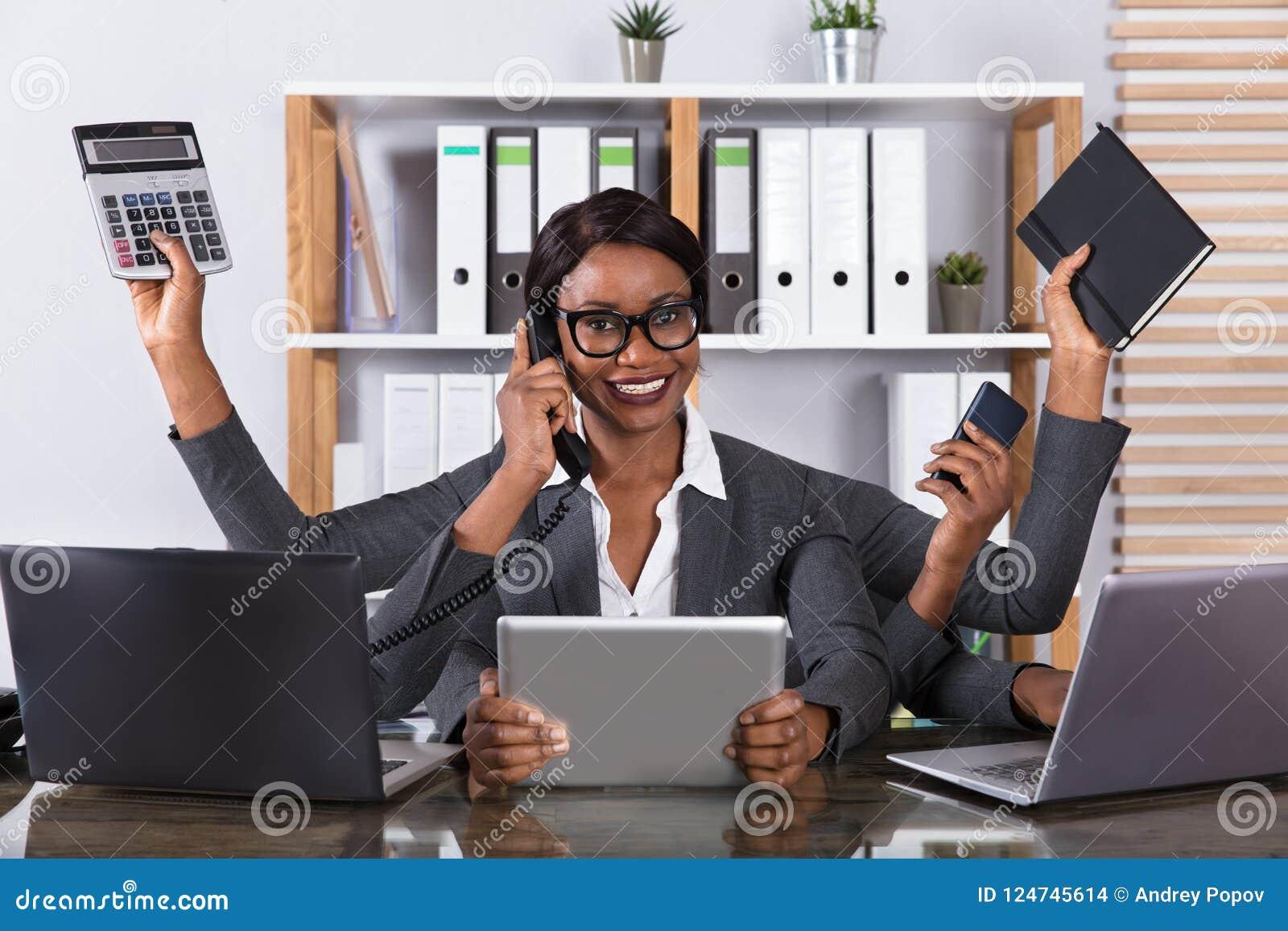 Trött kvinna som gör Multitaskingarbete på bärbara datorn