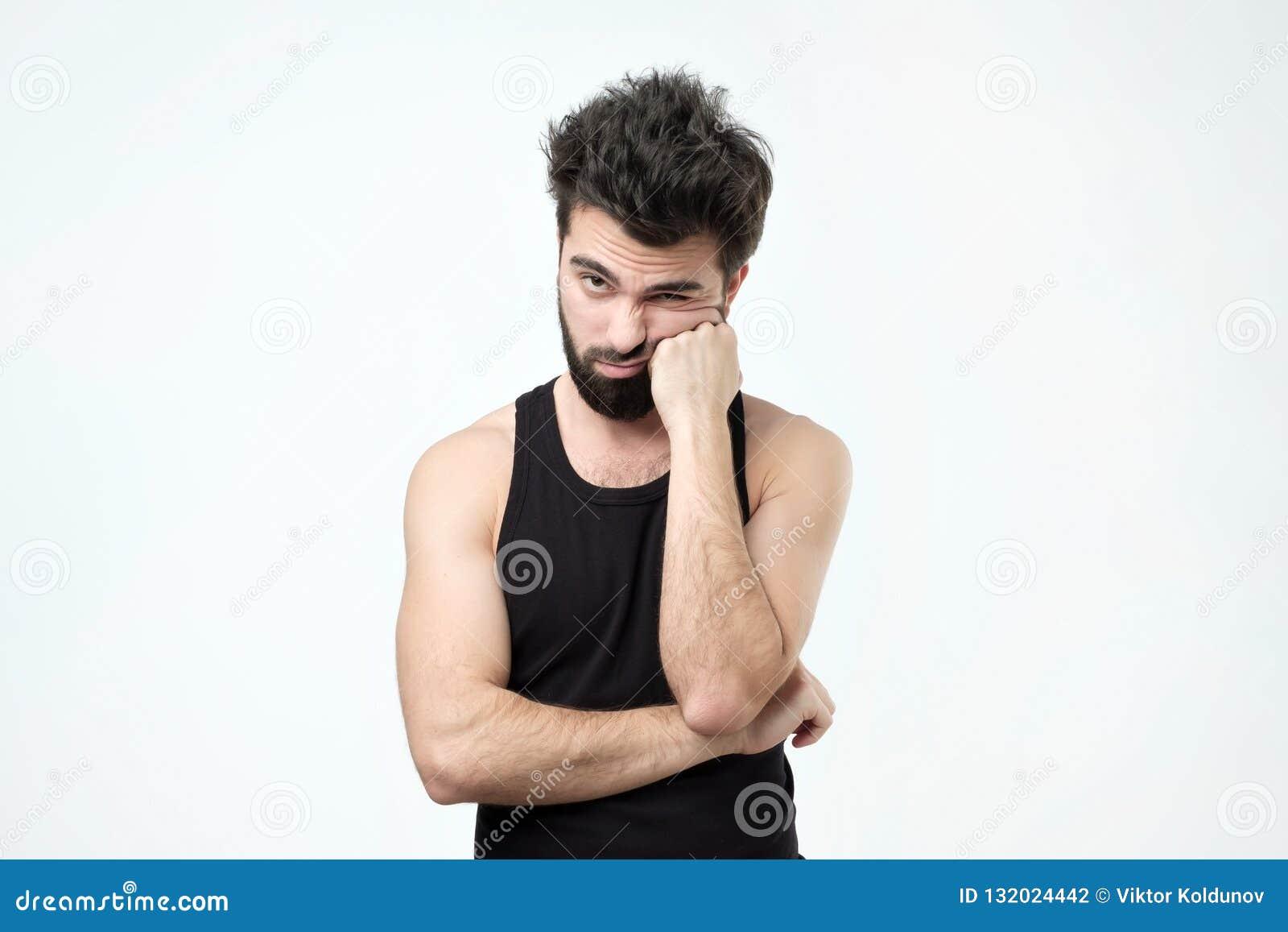 Trött latinamerikansk grabb med skägget och att vara evakuerat och önska att få vila mot grå bakgrund