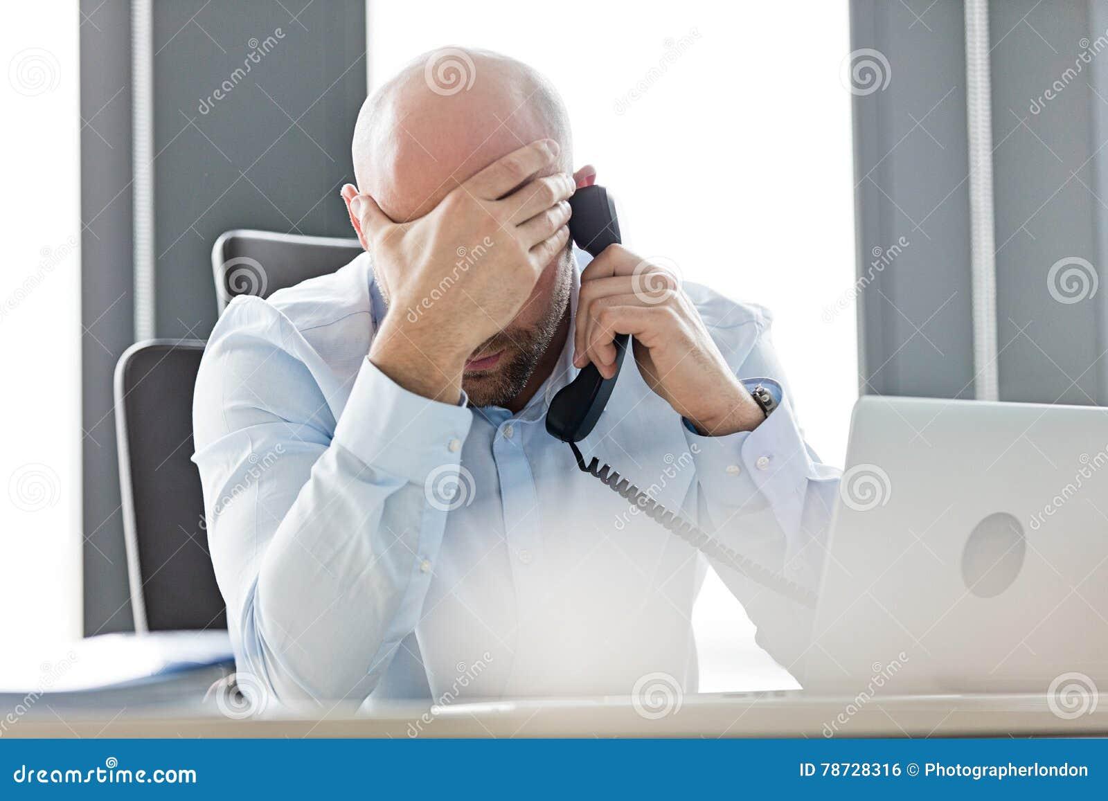 Trött mitt- vuxen affärsman som i regeringsställning använder landlinetelefonen på skrivbordet