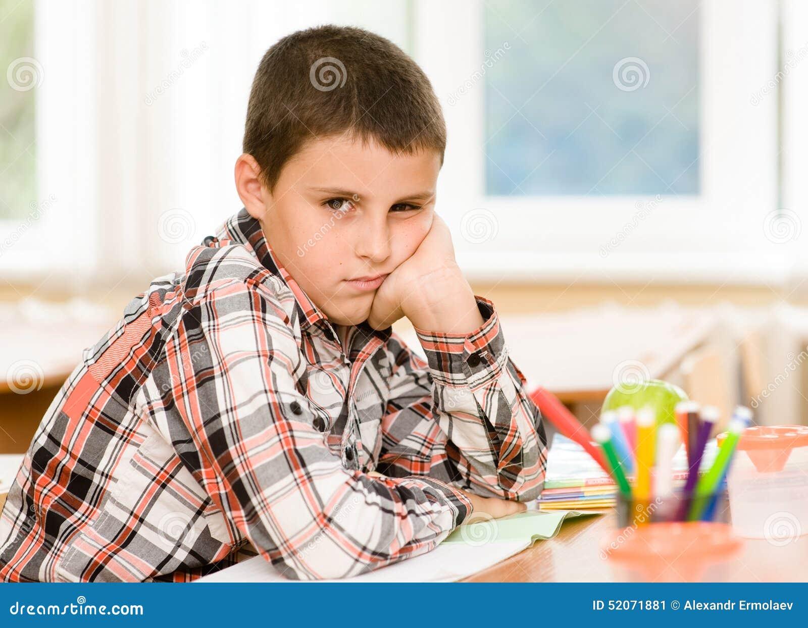 Trött skolpojke i klassrum