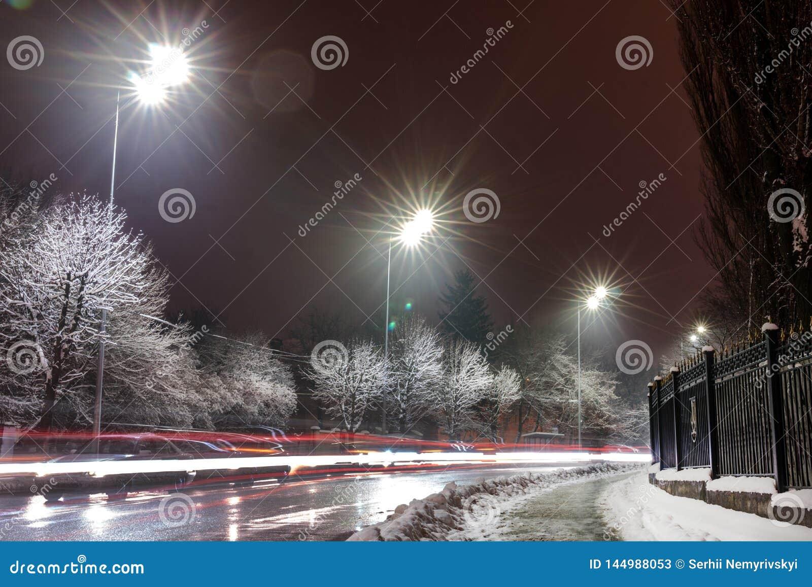 Tr?fego movente r?pido na noite Esta??o do inverno conceito da estrada, a remo??o de neve e de gelo, o perigo e a seguran?a do mo