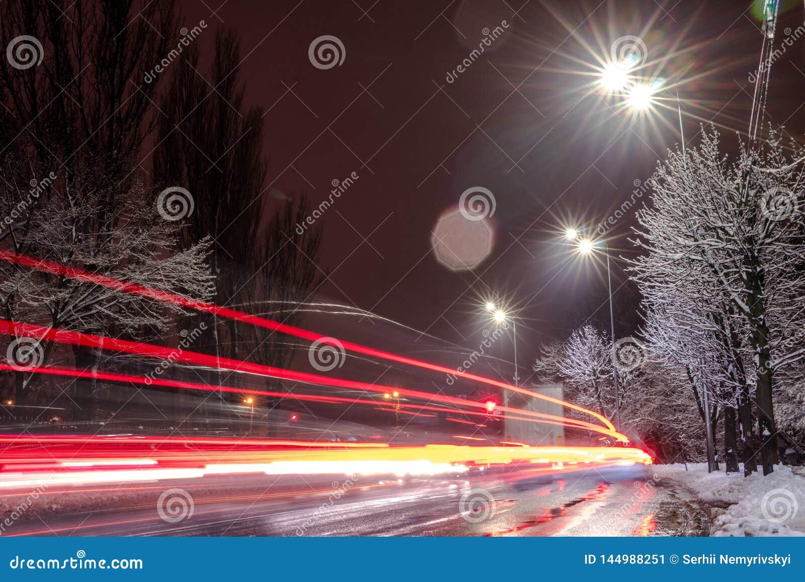 Tr?fico r?pido en la noche Estaci?n del invierno concepto del camino, el retiro de nieve y de hielo, el peligro y la seguridad de