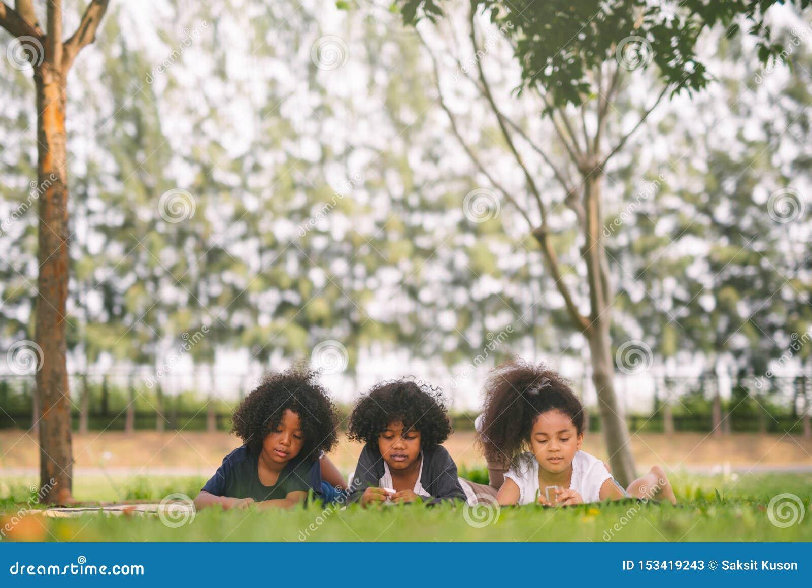 Tr?s amigos pequenos felizes que colocam na grama no parque crianças africanas americanas que jogam o brinquedo no parque