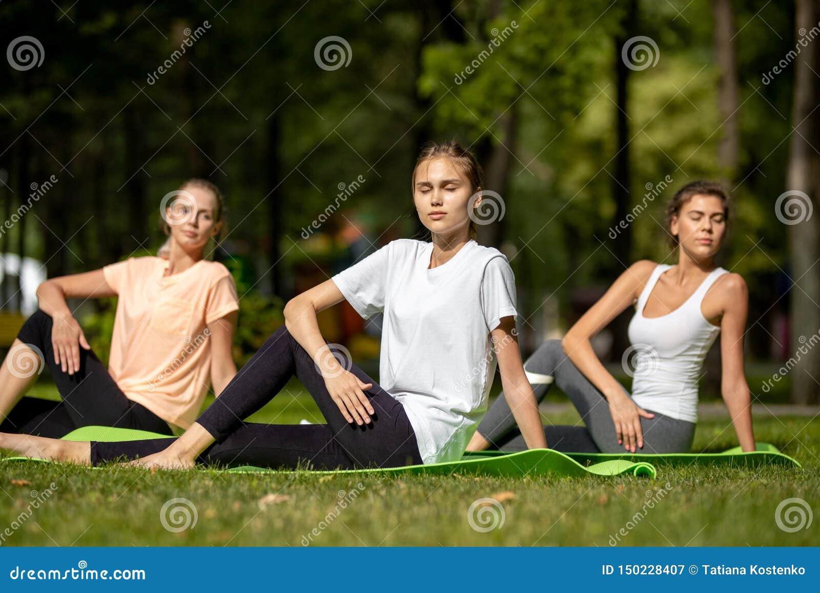Tr?s mo?as que fazem o estic?o em esteiras da ioga na grama verde no parque no ar livre