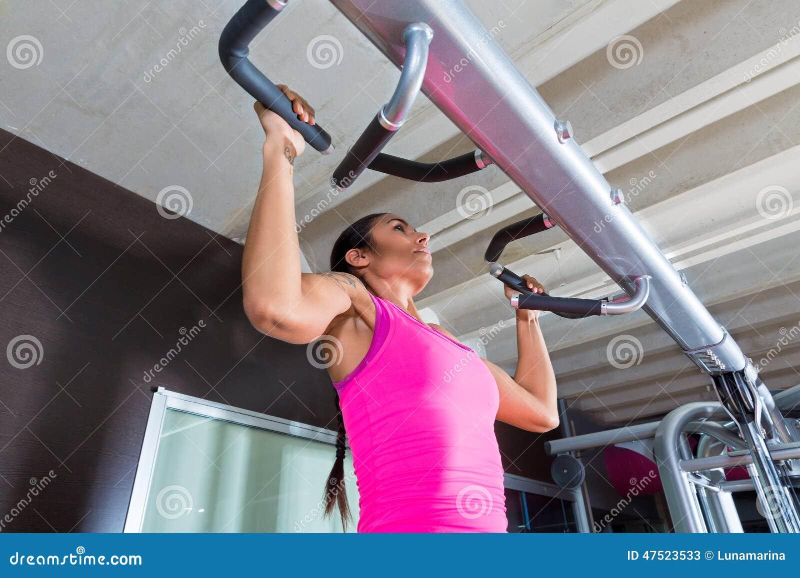 A tração levanta levanta a menina do exercício do exercício no gym