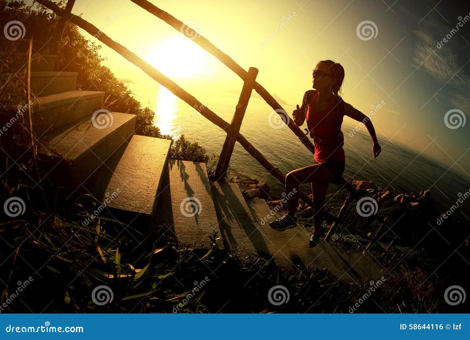 Traînée de coureur de femme de forme physique fonctionnant sur des escaliers de montagne de bord de la mer