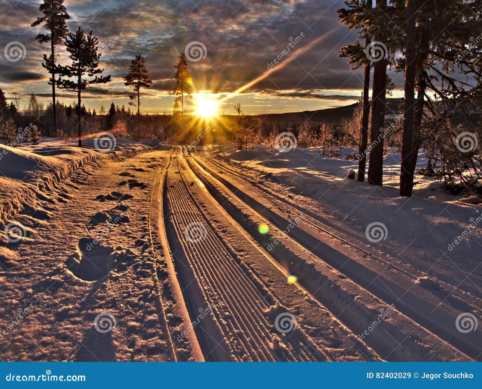 Traînées de ski avec des faisceaux du soleil