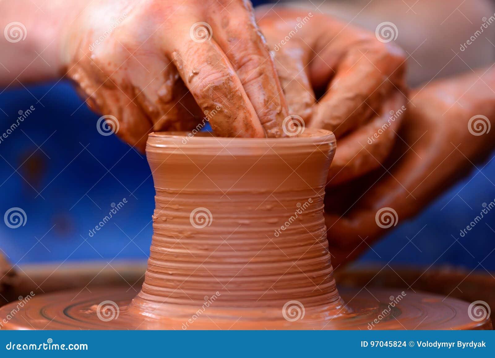 Traînez en faisant le pot en céramique sur la roue de poterie