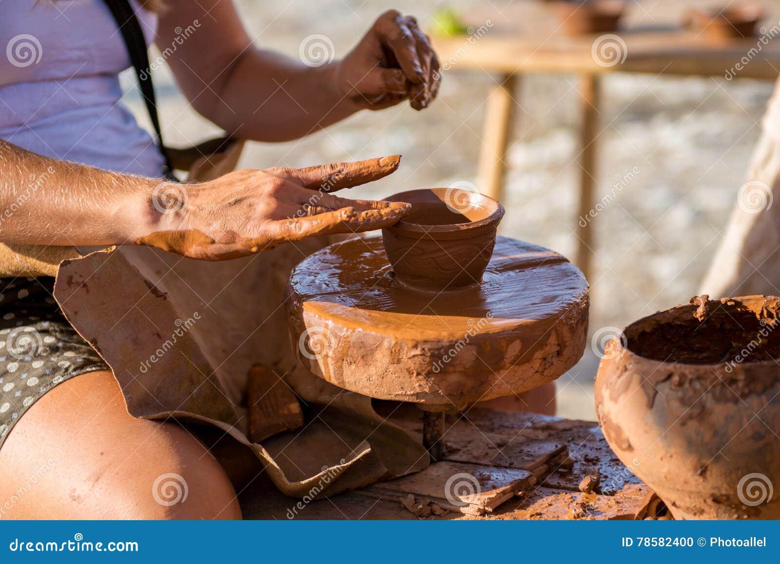 Traînez les mains faisant en argile sur la roue de poterie fait le pot